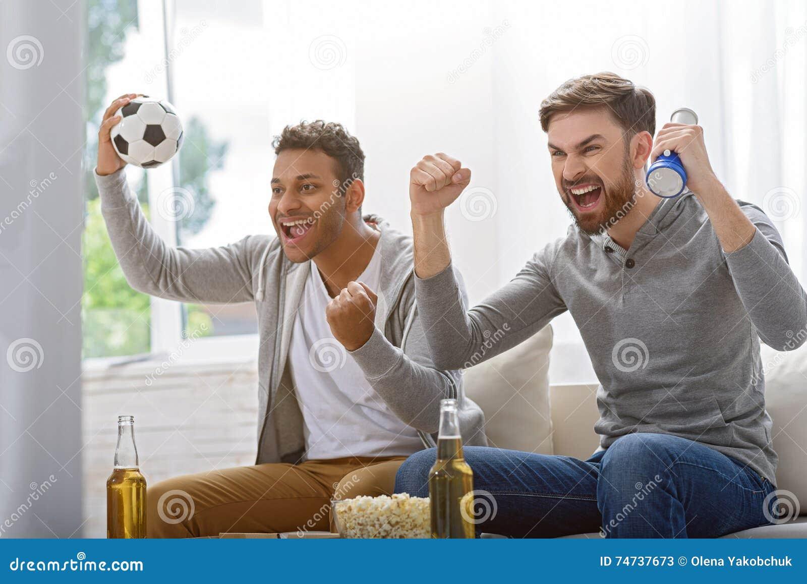 Φίλοι που απολαμβάνουν το ποδόσφαιρο στη TV
