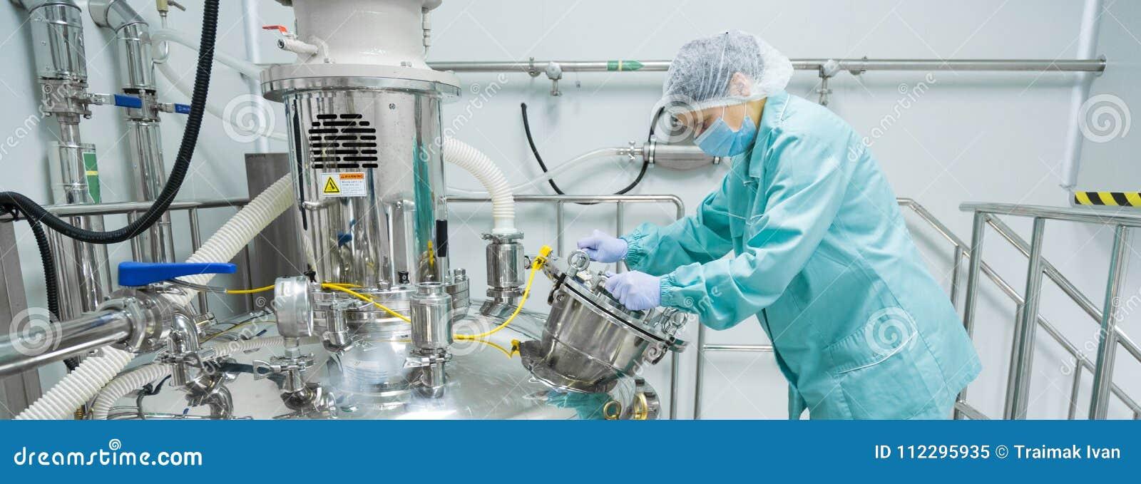 Φαρμακευτικός εργαζόμενος γυναικών εργοστασίων στη λειτουργούσα γραμμή παραγωγής προστατευτικής ενδυμασίας στο αποστειρωμένο περι