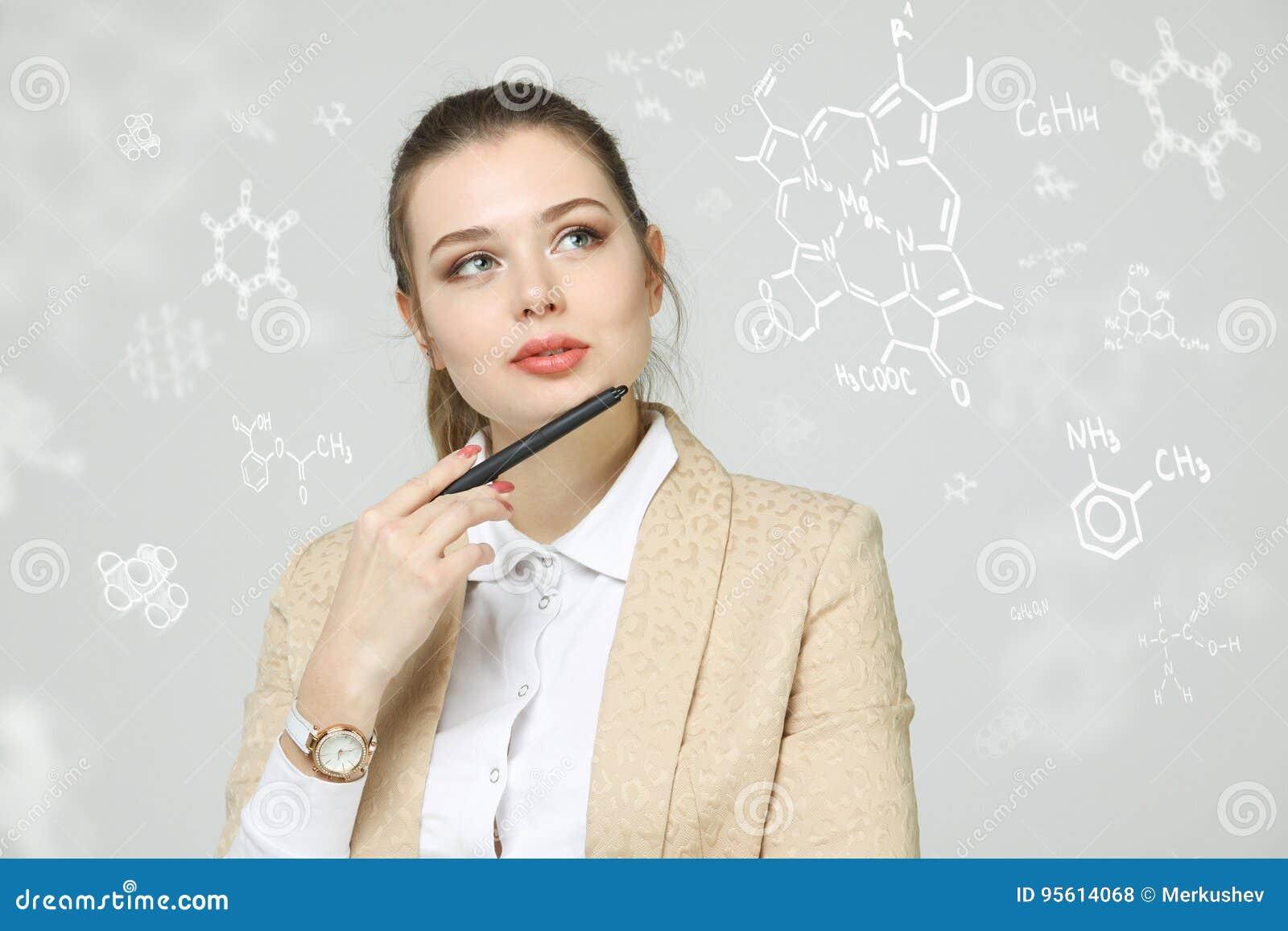 Φαρμακοποιός γυναικών με stylus ή μάνδρα που λειτουργεί με τους χημικούς τύπους στο γκρίζο υπόβαθρο