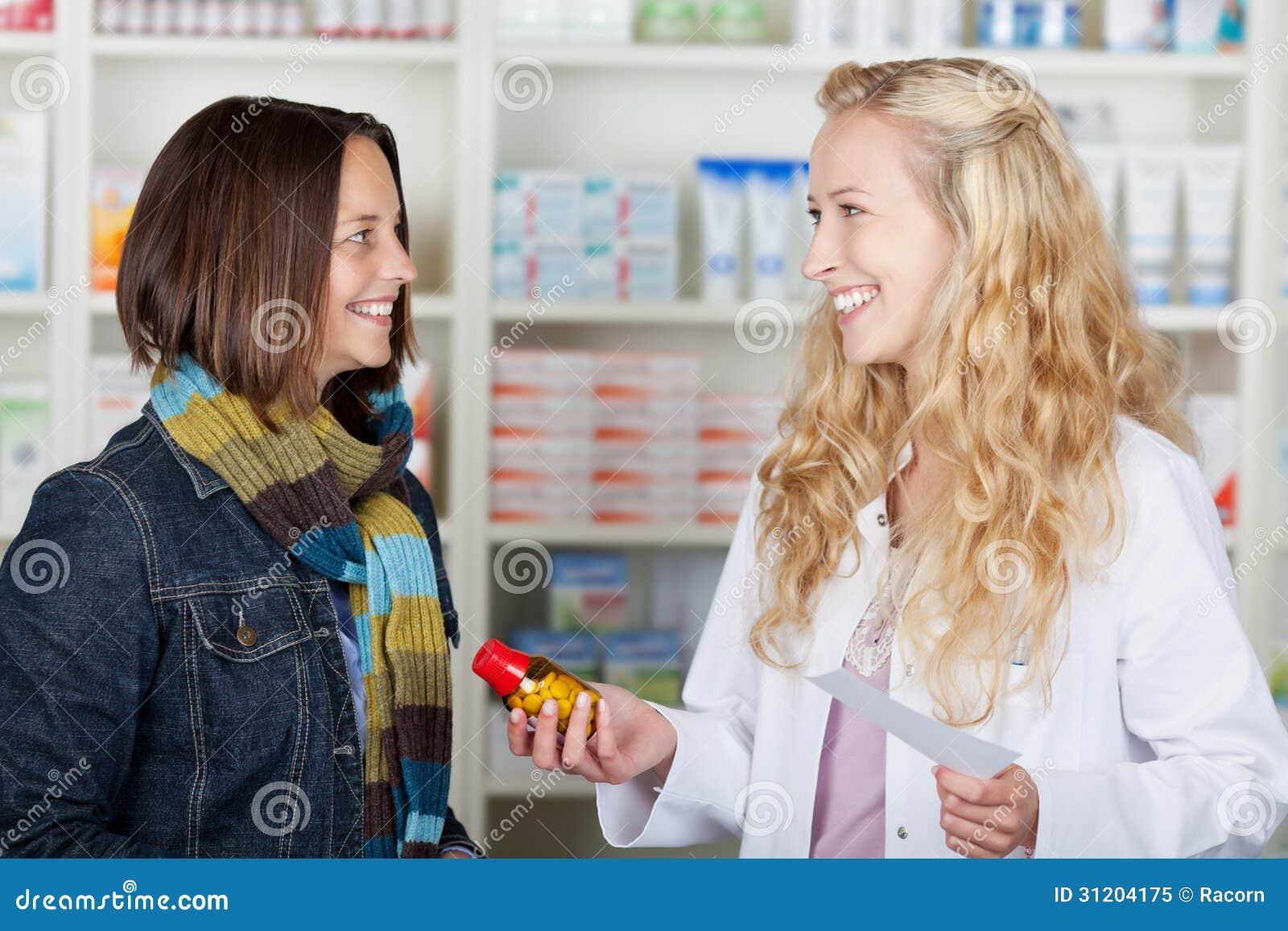 Φαρμακοποιός που δίνει το μπουκάλι ιατρικής στο θηλυκό πελάτη