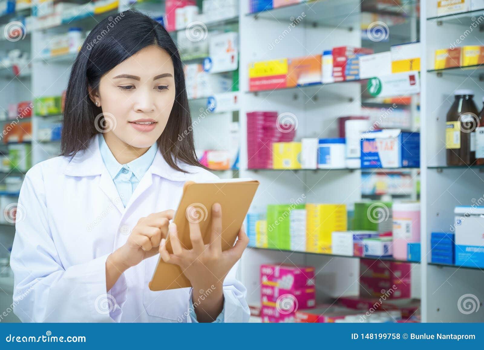 Φαρμακοποιός που απασχολείται με έναν υπολογιστή ταμπλετών στην εκμετάλλευση φαρμακείων σε το στο χέρι της διαβάζοντας τις πληροφ