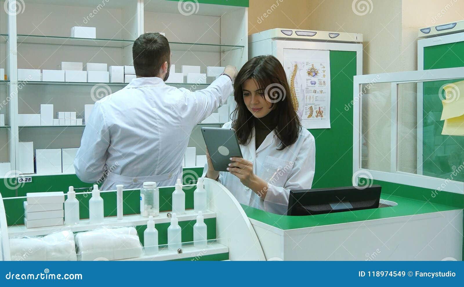 Φαρμακοποιός που απασχολείται με μια ταμπλέτα στην εκμετάλλευση φαρμακείων σε το στο χέρι της διαβάζοντας τις πληροφορίες