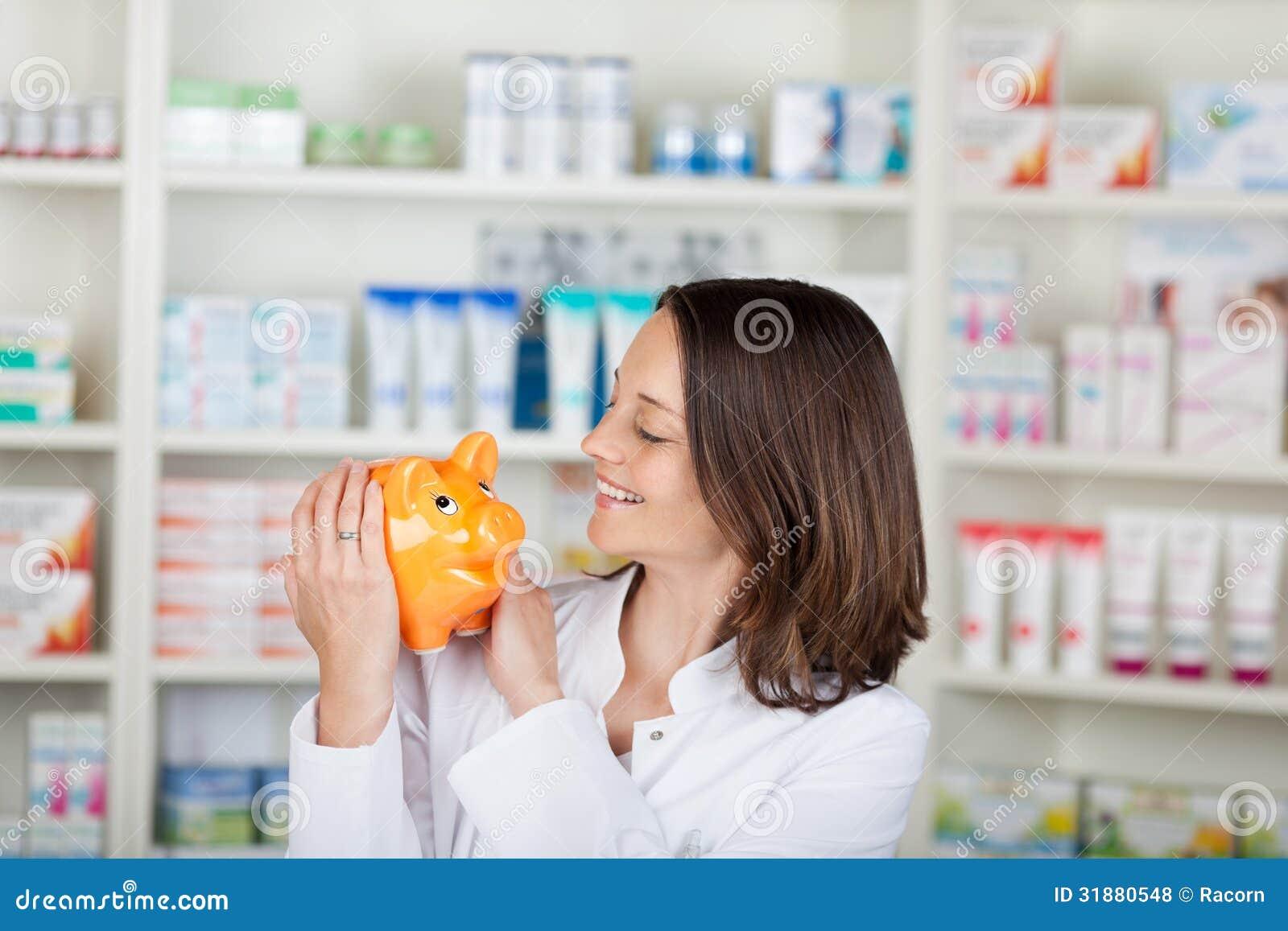 Φαρμακοποιός που εξετάζει Piggybank στο φαρμακείο