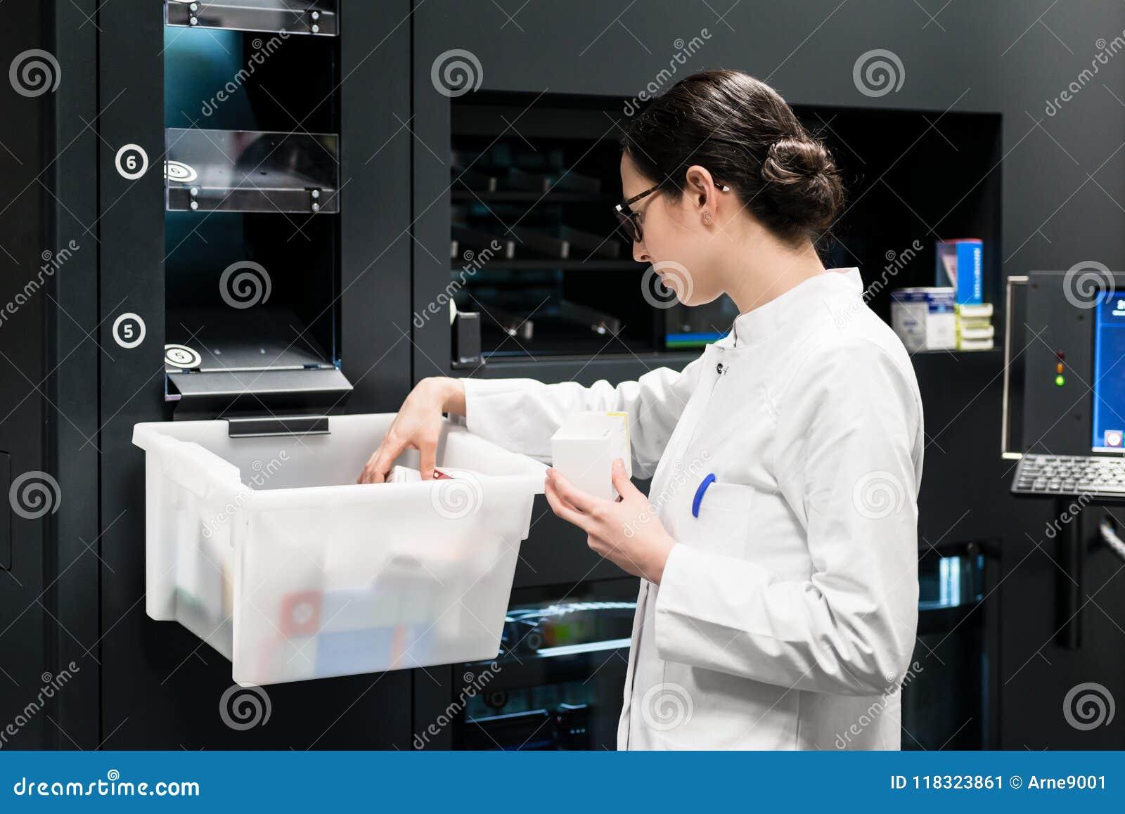 Φαρμακοποιός που επιλέγει τα καλύτερα φάρμακα κατά τη διάρκεια της εργασίας στο φαρμακείο
