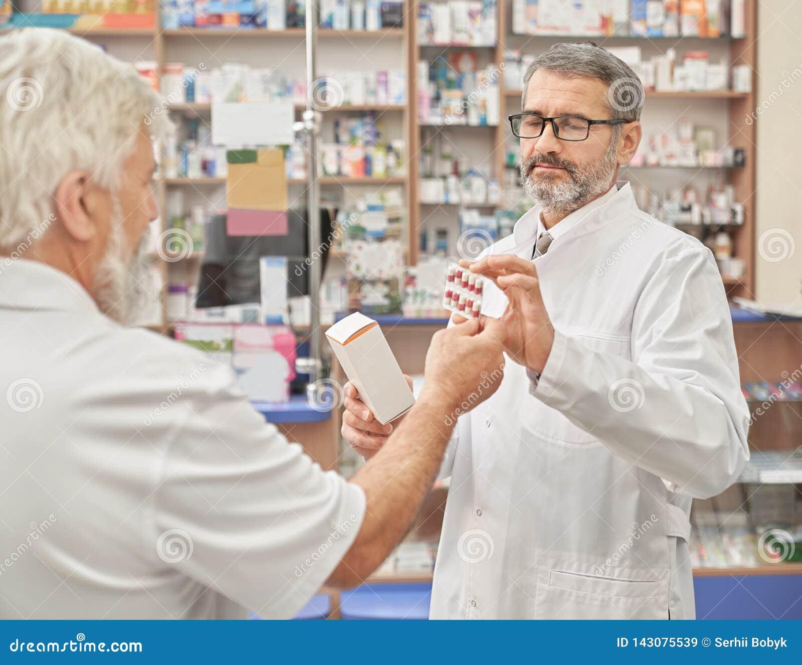 Φαρμακοποιός που προσφέρει τα φάρμακα στον παλαιό πελάτη στο φαρμακείο