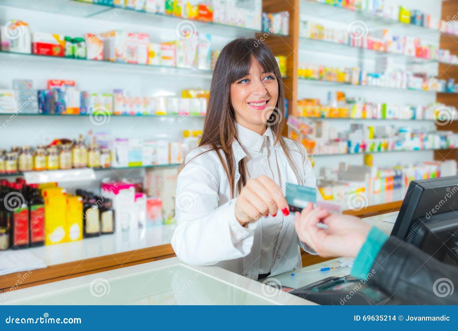 Φαρμακοποιός που προτείνει το ιατρικό φάρμακο στον αγοραστή στο φαρμακείο φαρμακείων