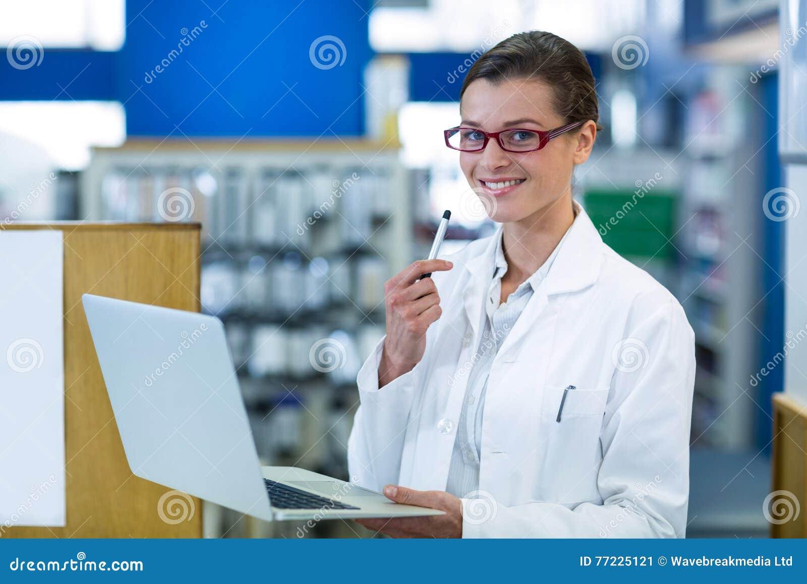 Φαρμακοποιός που χρησιμοποιεί το lap-top στο φαρμακείο