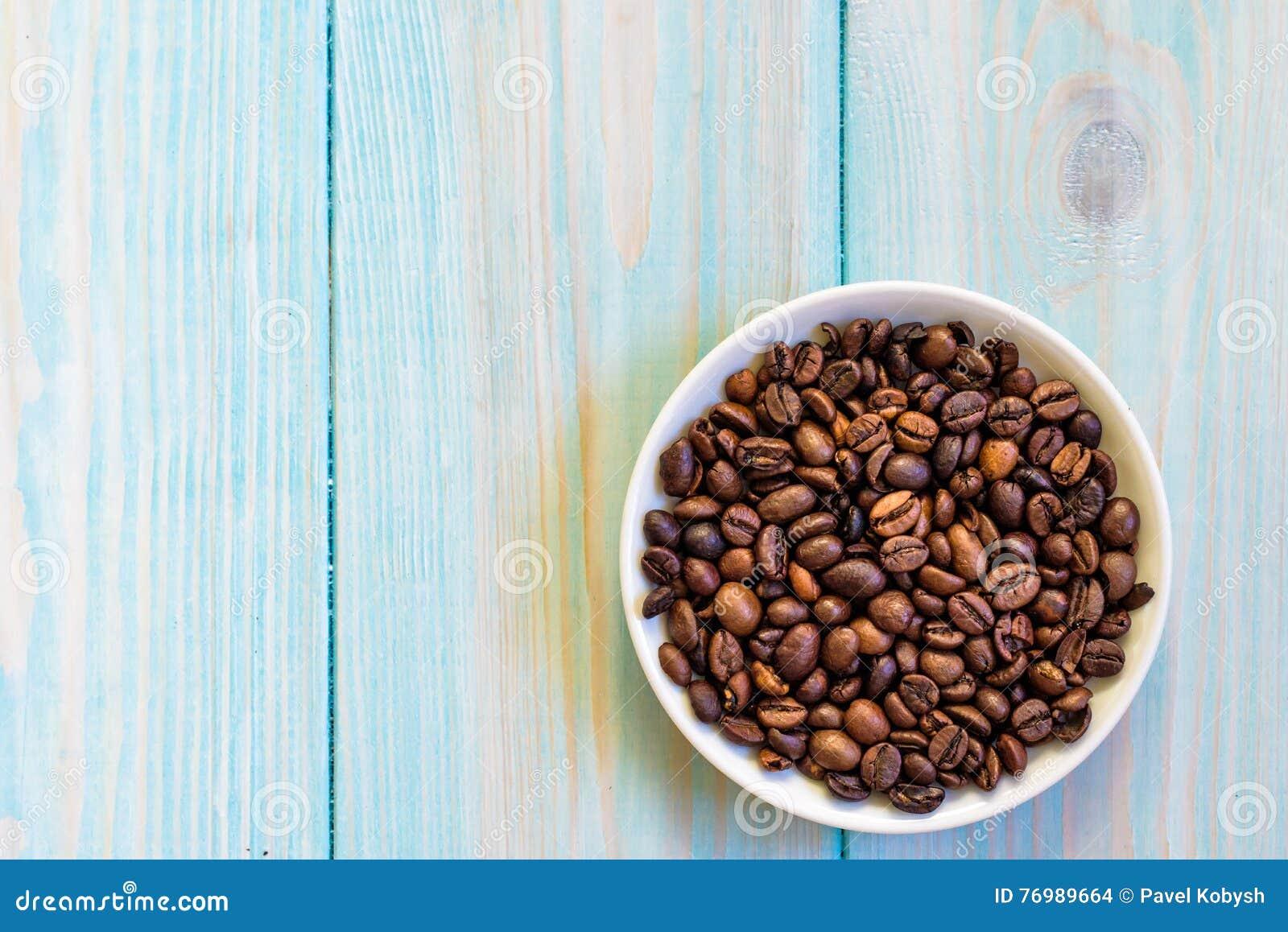 Φασόλια καφέ στο πιάτο Επίπεδος βάλτε στο αγροτικό ανοικτό μπλε ξύλινο υπόβαθρο