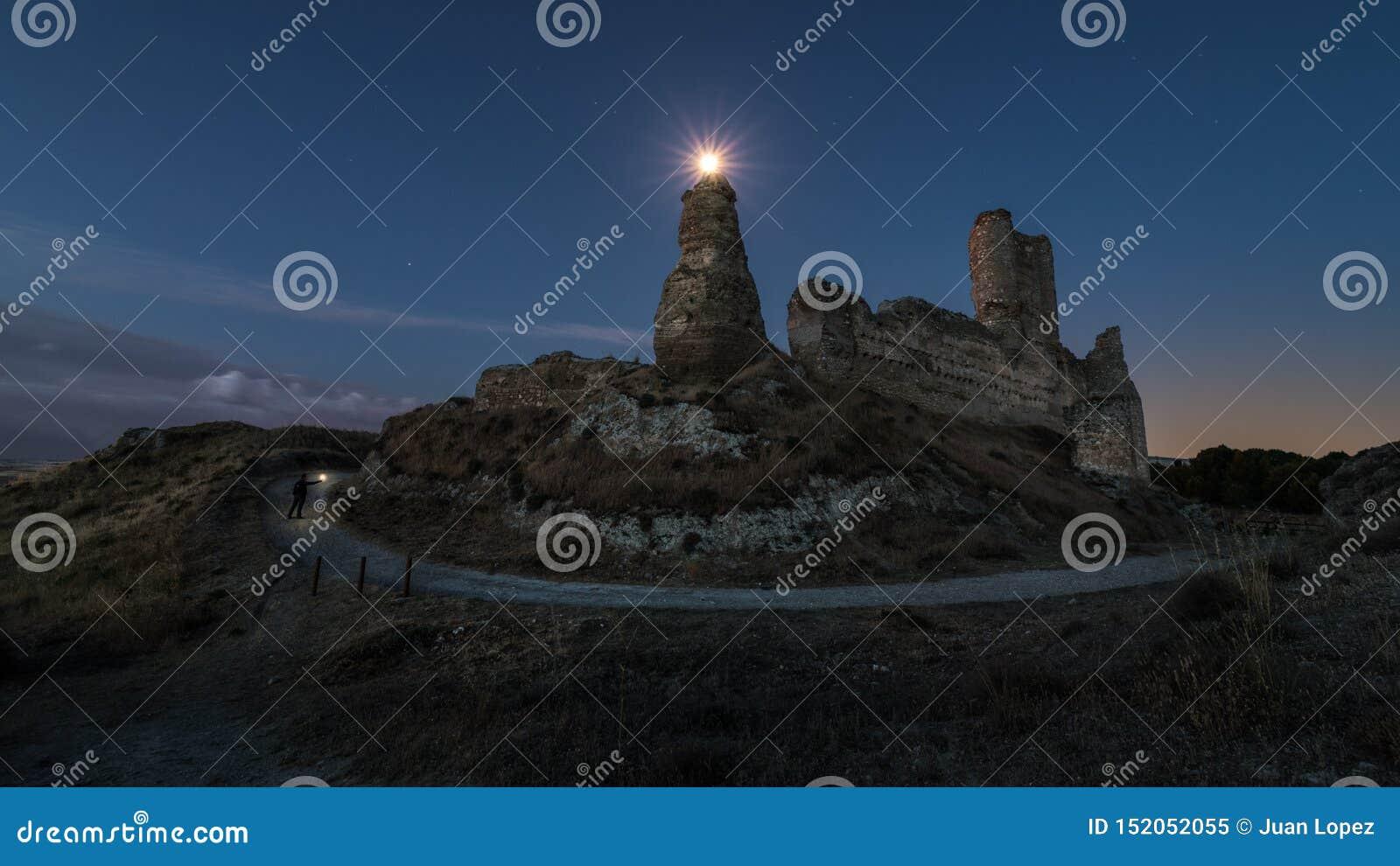 Φεγγάρι σε ένα λυκόφως πέρα από τις καταστροφές ενός παλαιού κάστρου