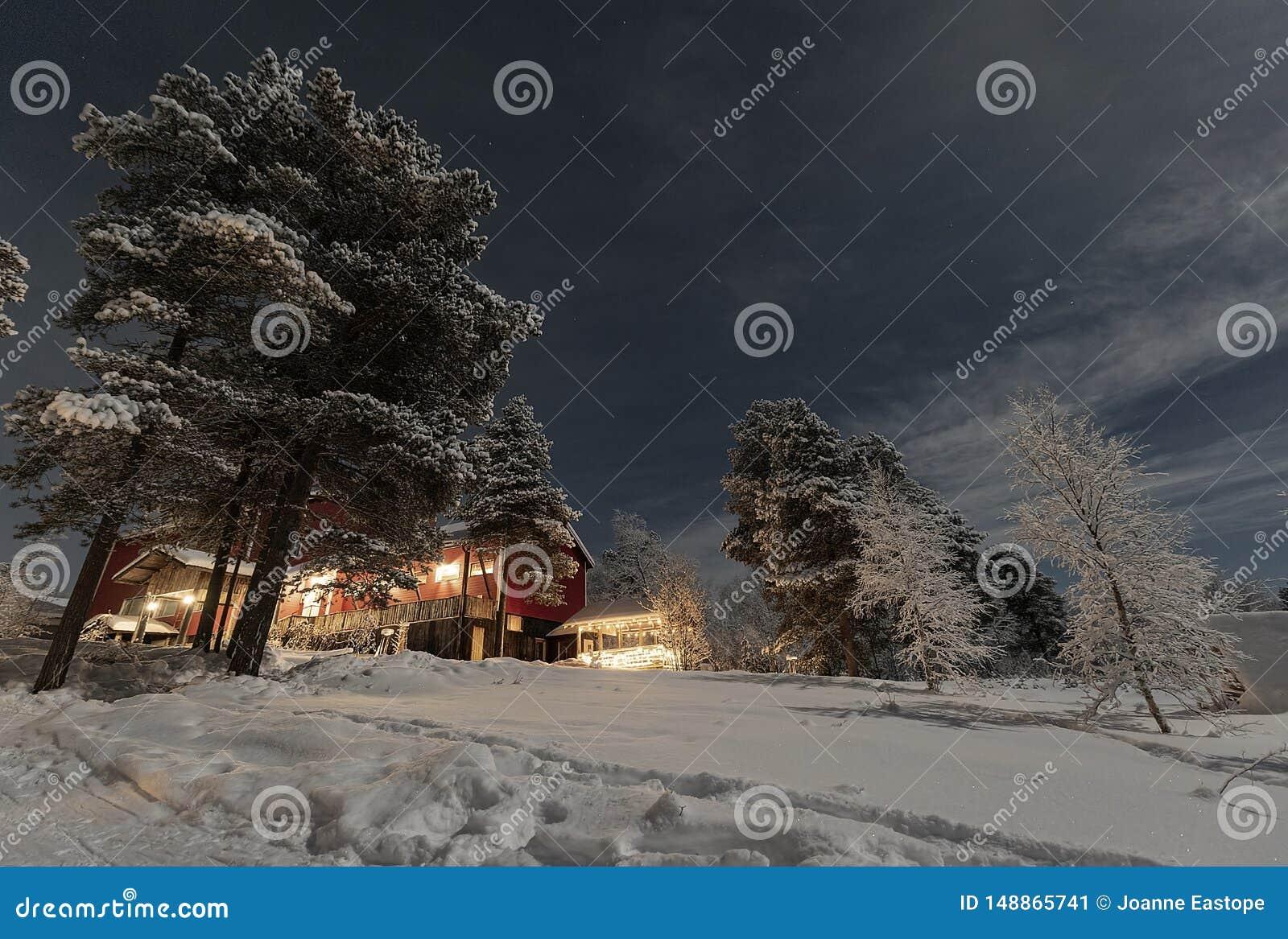 Φεγγαρόφωτο χειμερινό τοπίο Lappish, φω τα υποδοχής από το ξενοδοχείο