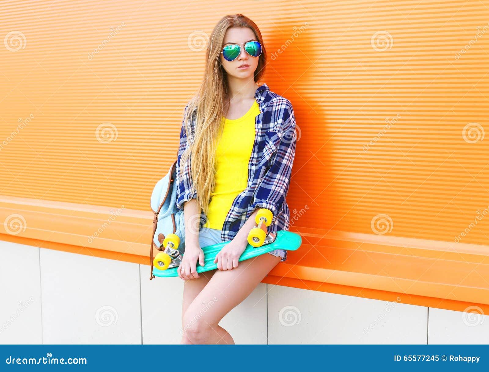 Φθορά κοριτσιών μόδας αρκετά δροσερή γυαλιά ηλίου με skateboard πέρα από ζωηρόχρωμο