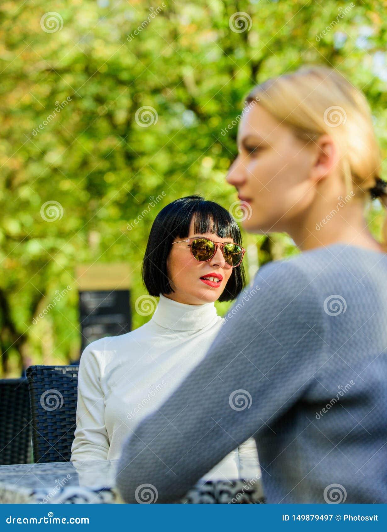 Φιλία ή ανταγωνισμός Πλήρης εμπιστοσύνης επικοινωνία Οι φίλοι κοριτσιών πίνουν τη συζήτηση καφέ Συνομιλία του πεζουλιού καφέδων δ