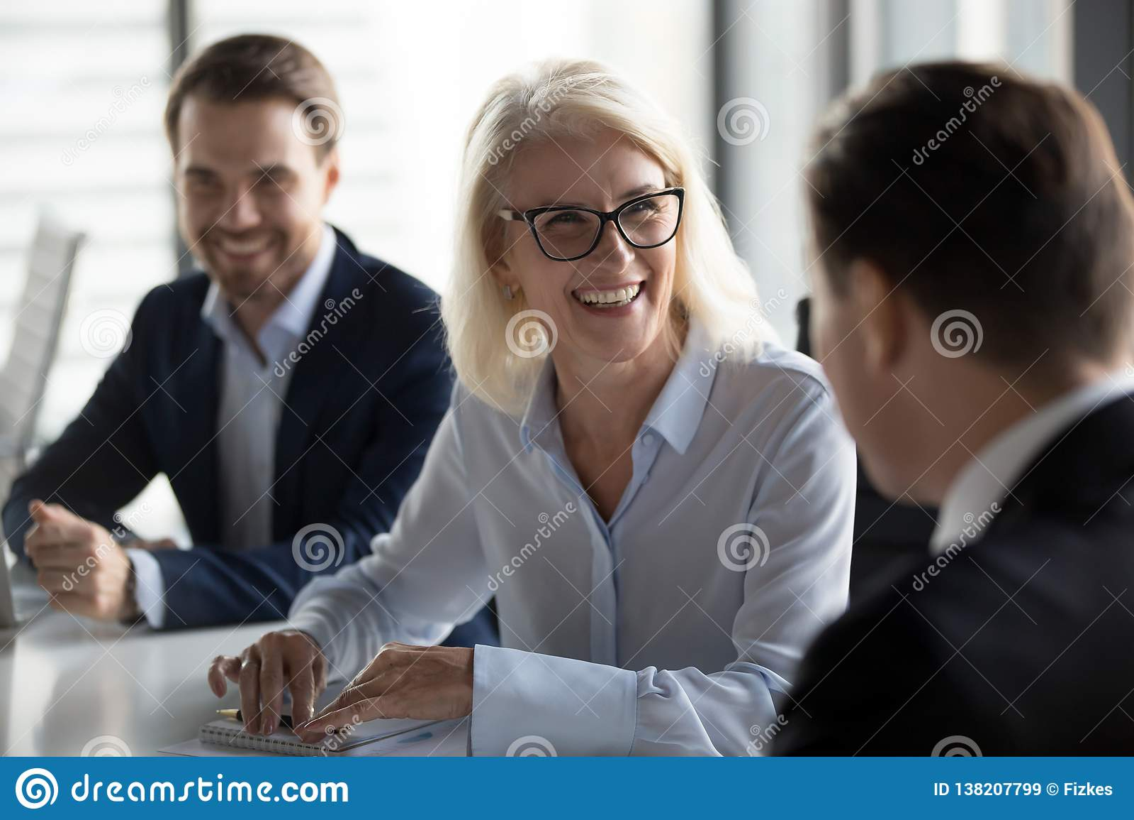 Φιλικός μέσος ηλικίας θηλυκός ηγέτης που γελά στην επιχειρησιακή συνεδρίαση ομάδας