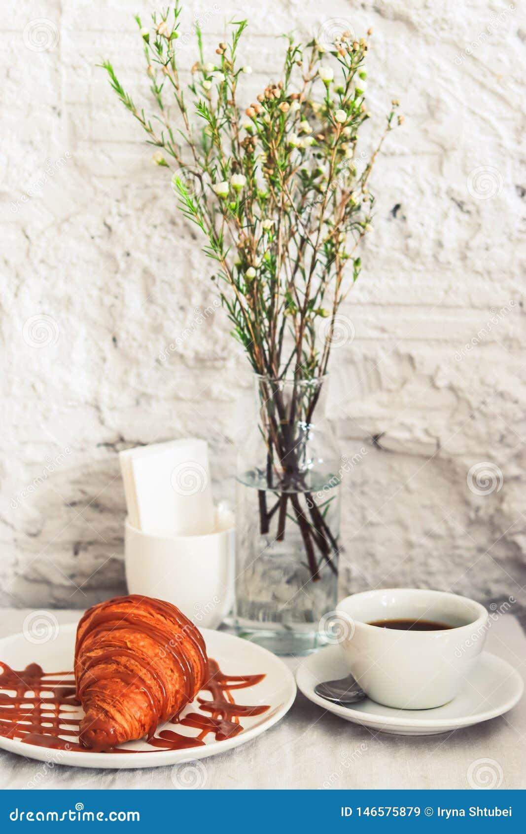 Φλιτζάνι του καφέ με croissant