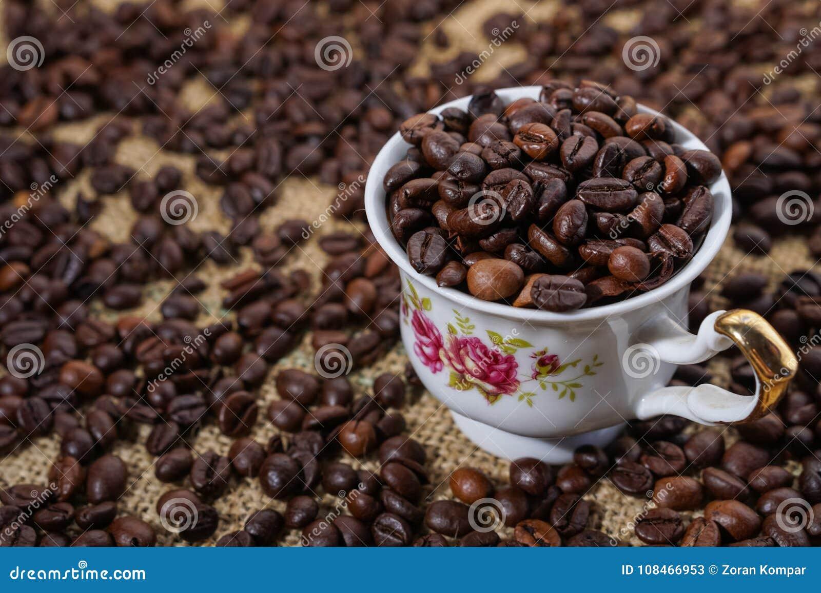 Φλυτζάνι καφέ τα πορφυρά λουλούδια που γεμίζουν με με τα φασόλια