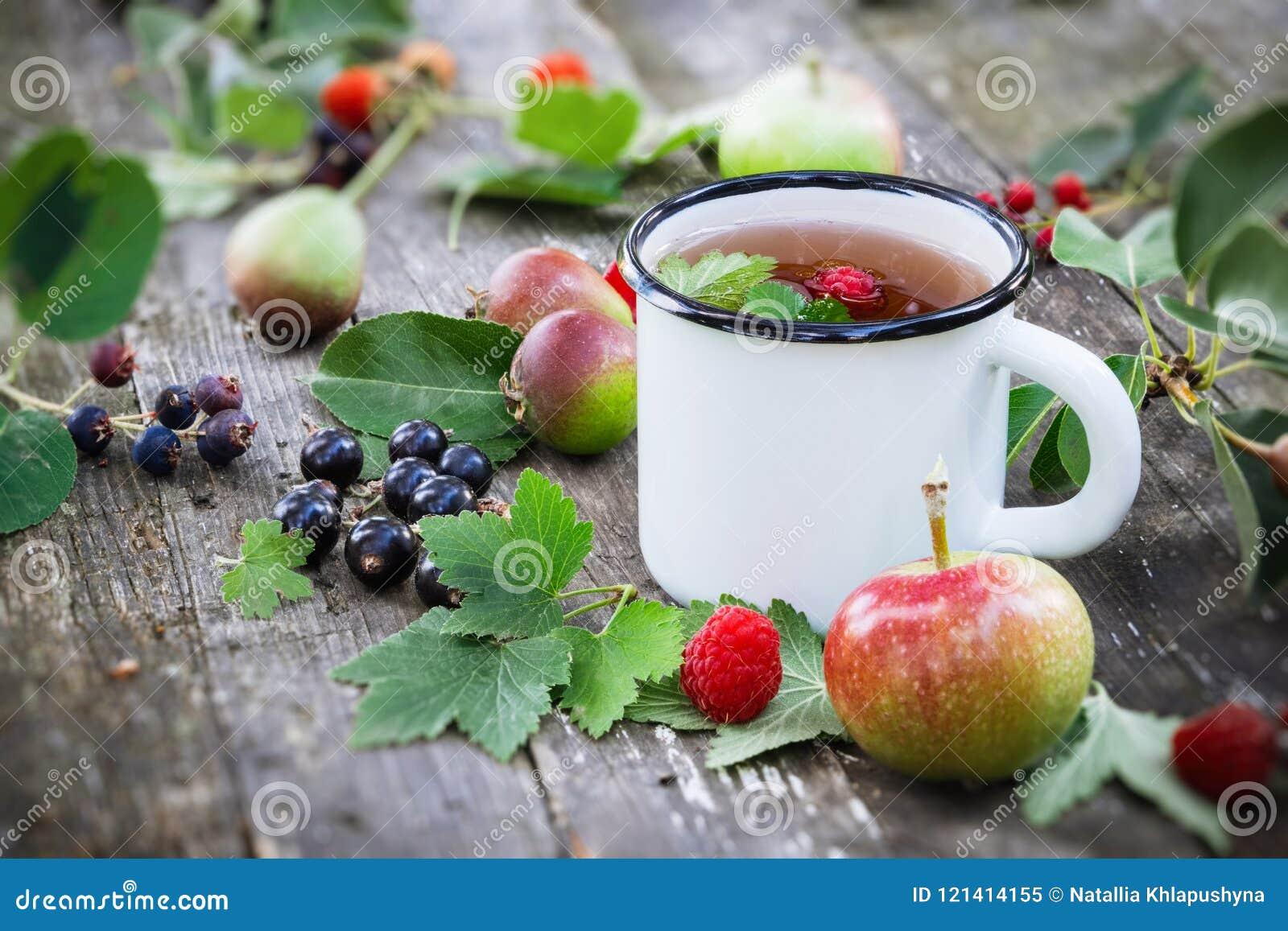 Φλυτζάνι του τσαγιού φρούτων με τα μήλα, τα αχλάδια, τα σμέουρα και τα μούρα μαύρων σταφίδων στον ξύλινο πίνακα υπαίθρια