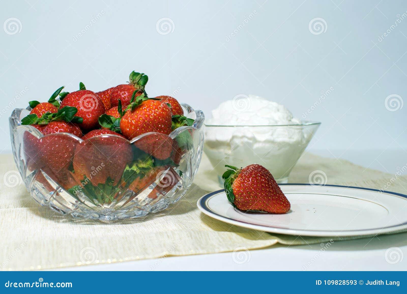Φράουλες και κτυπημένη κρέμα και ένα πιάτο με μια φράουλα