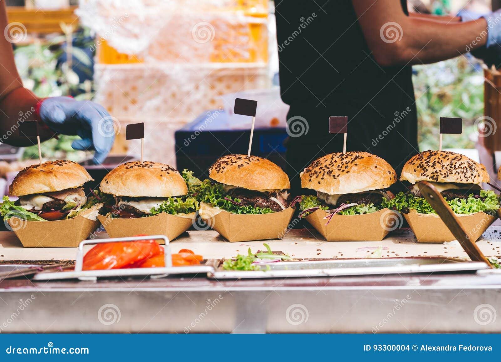 Φρέσκα εύγευστα ψημένα στη σχάρα burgers στον πίνακα Burger φεστιβάλ