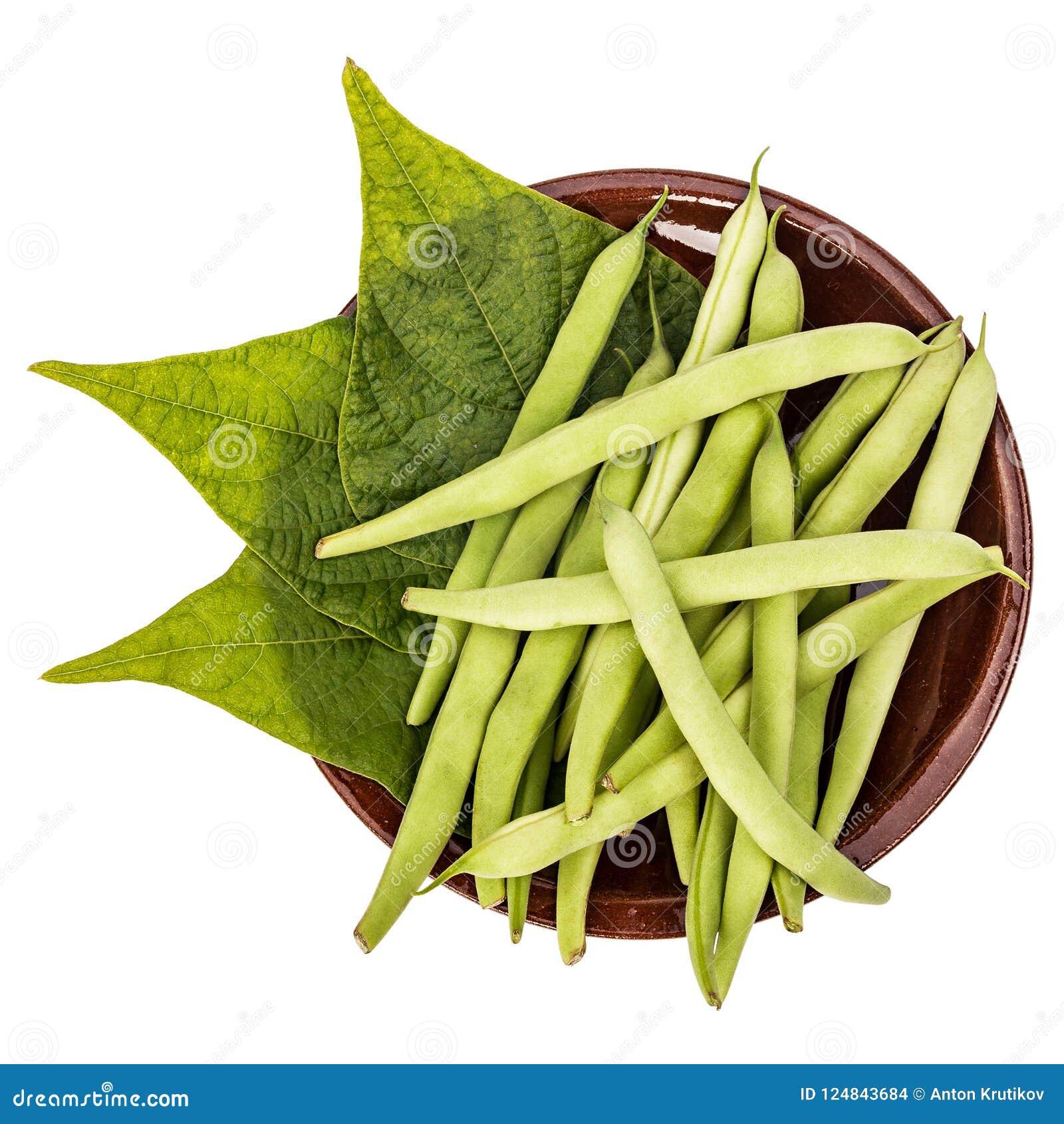 Φρέσκα πράσινα φασόλια και φύλλα σε ένα πιάτο αργίλου σε έναν πίνακα