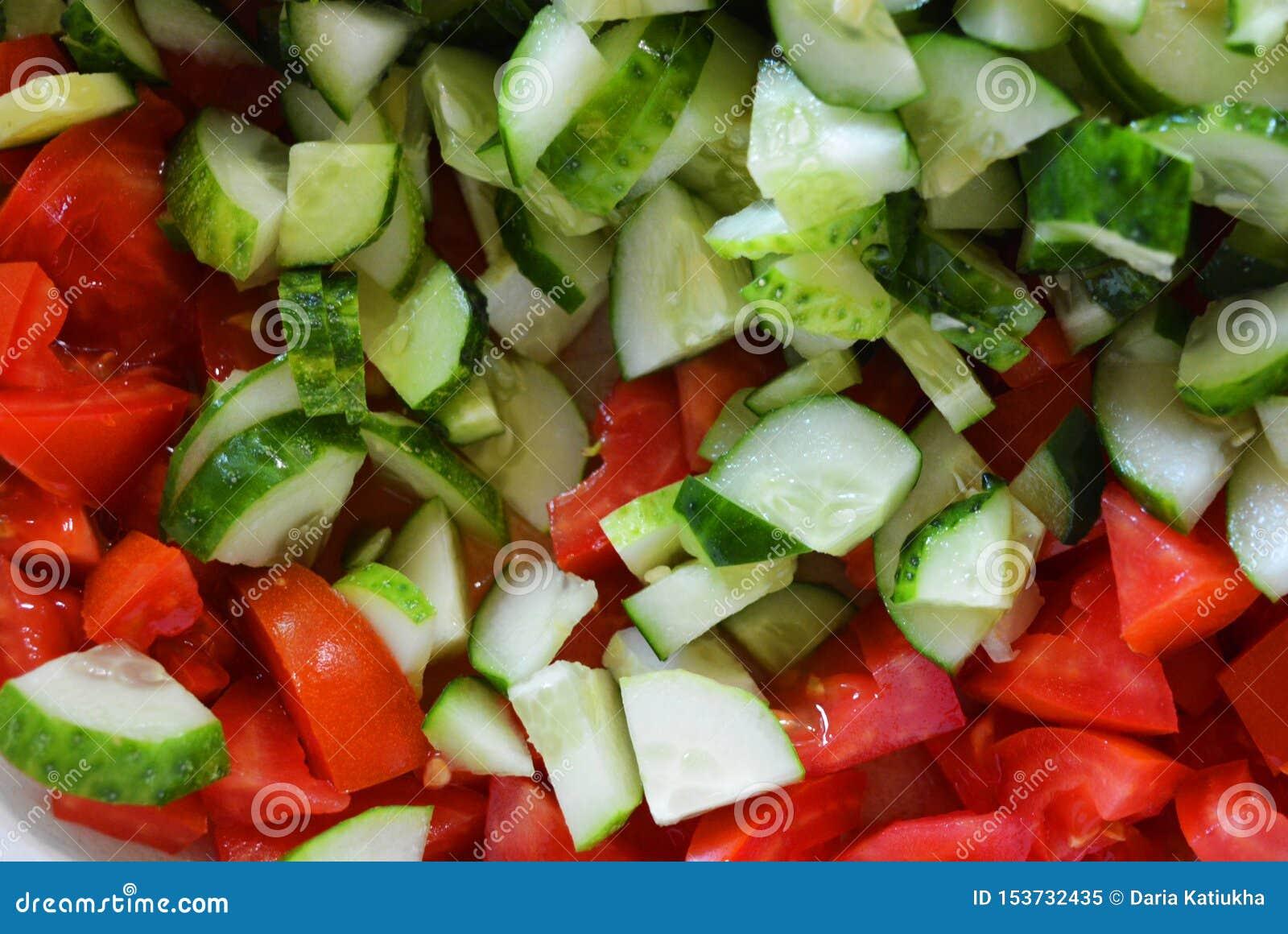 Φρέσκα υγιή λαχανικά, μικρές φέτες των πράσινων αγγουριών και κόκκινες ντομάτες για τη θερινή σαλάτα, συστατικά για τη σαλάτα