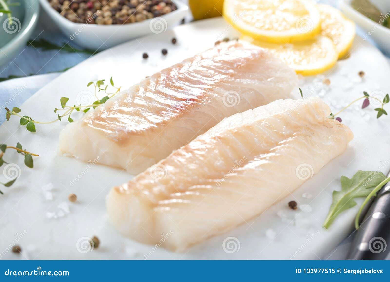 Φρέσκα ψάρια, ακατέργαστες λωρίδες βακαλάων με την προσθήκη των χορταριών και λεμόνι