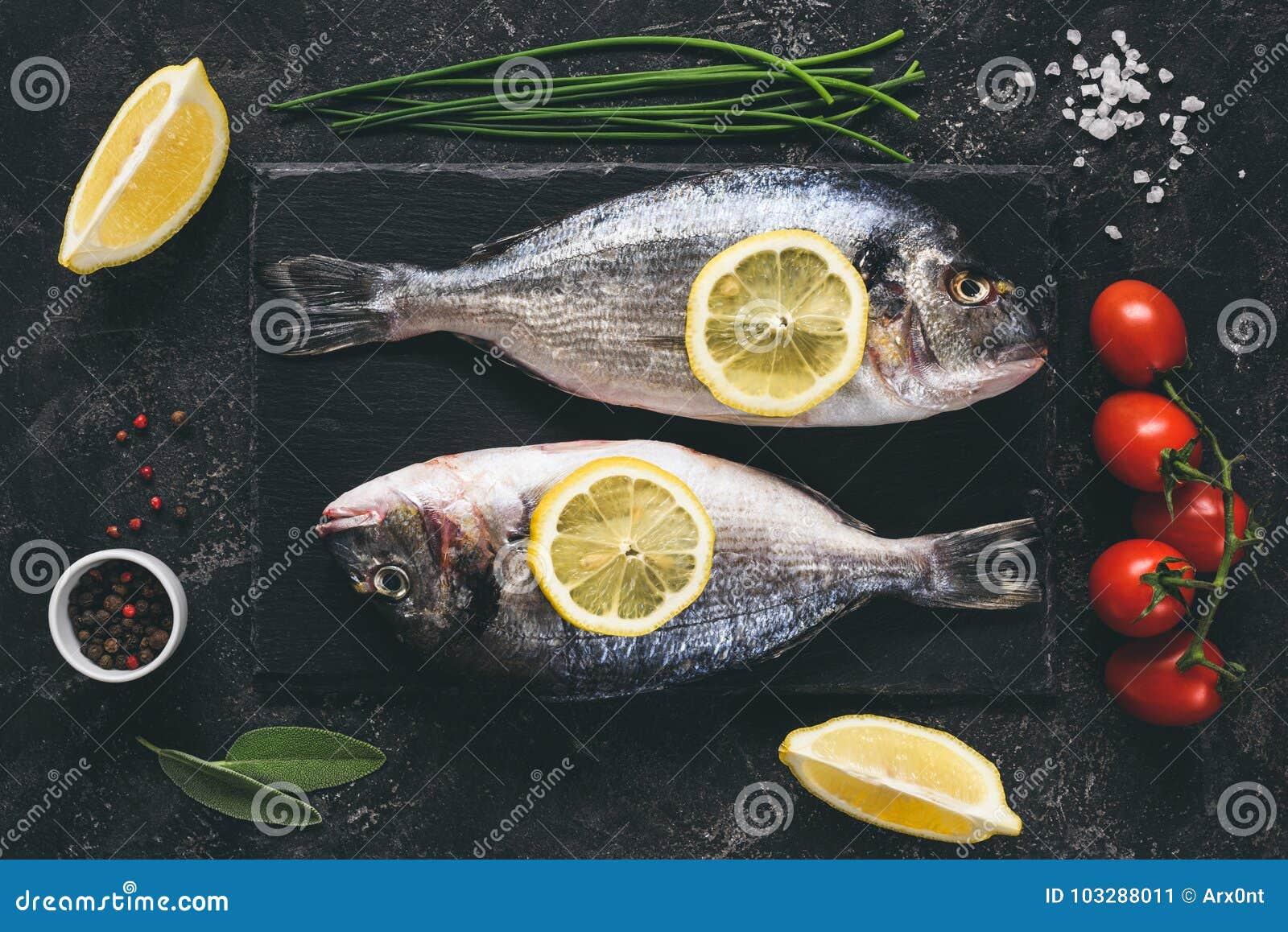 Φρέσκα ψάρια με τα καρυκεύματα, τα λαχανικά και τα χορτάρια στο υπόβαθρο πλακών έτοιμο για το μαγείρεμα