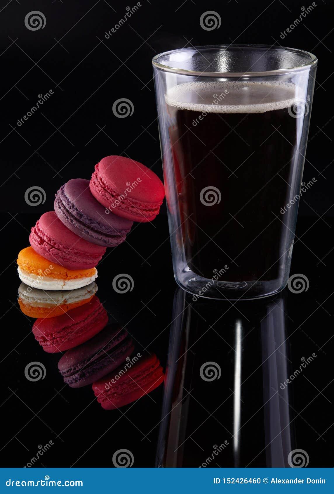 Φρέσκα macarons των διαφορετικών χρωμάτων και των γεύσεων και ένα ποτήρι του καφέ espresso σε ένα μαύρο υπόβαθρο
