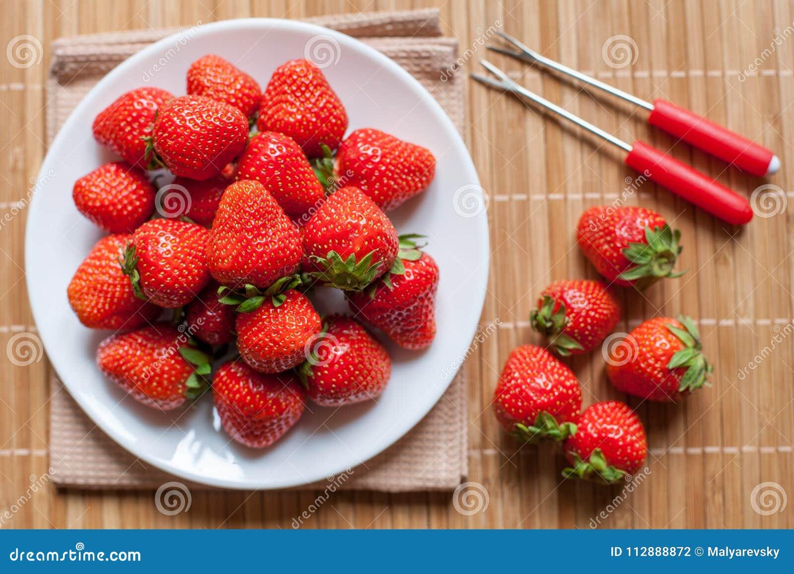 Φρέσκες φράουλες σε ένα κύπελλο στον ξύλινο πίνακα