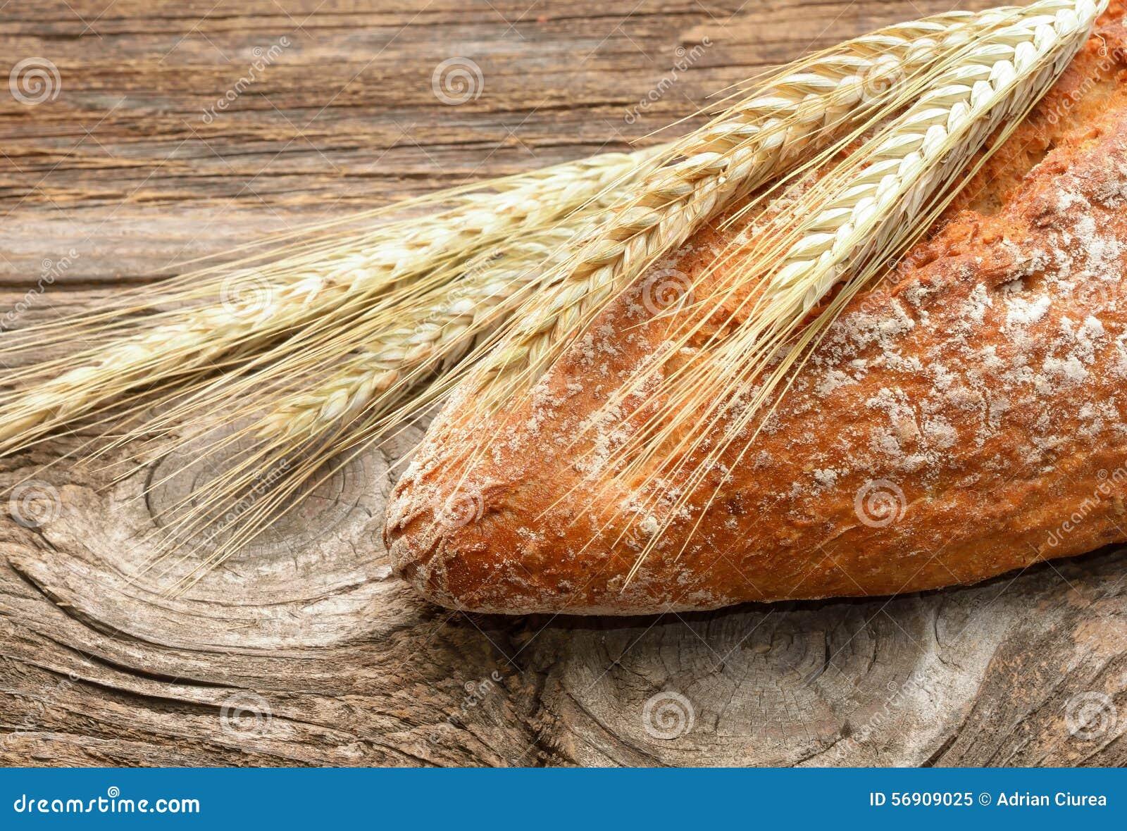 Φρέσκοι ψωμί και σίτος στο ξύλινο υπόβαθρο