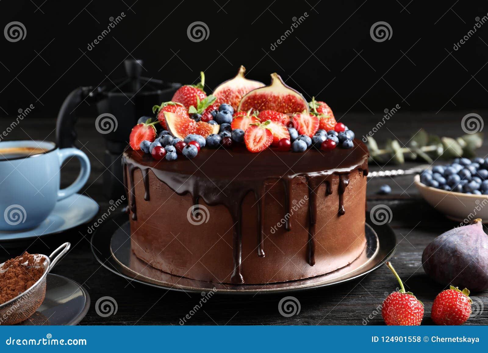 Φρέσκο εύγευστο σπιτικό κέικ σοκολάτας με τα μούρα στον πίνακα στο σκοτεινό κλίμα