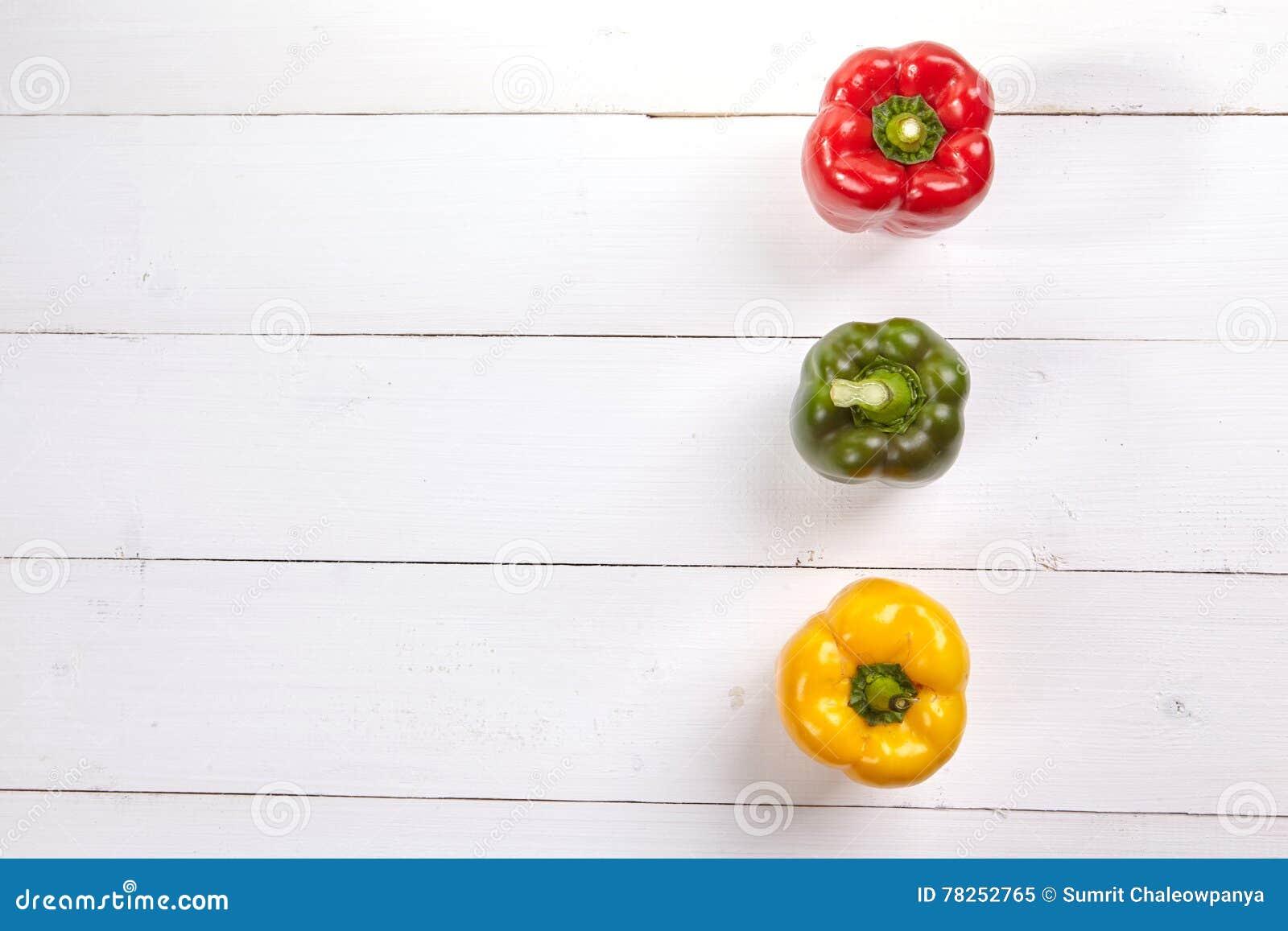 Φρέσκο ζωηρόχρωμο κιβώτιο πιπεριών κουδουνιών στον ξύλινο πίνακα