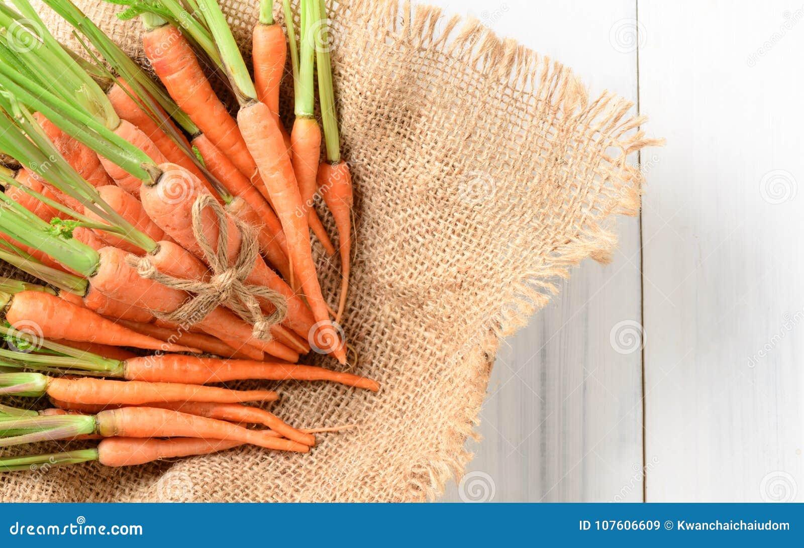 Φρέσκο καρότο, καρότο μωρών στο σάκο και άσπρο ξύλο