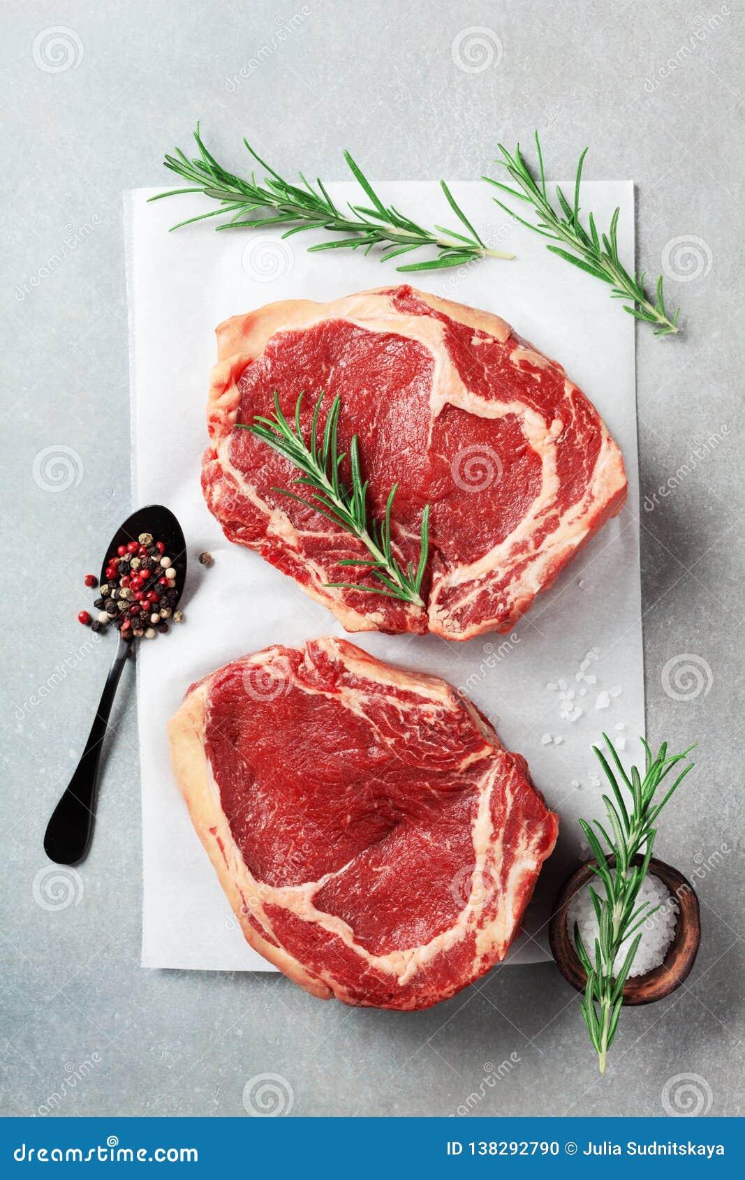 Φρέσκο κρέας στην άποψη επιτραπέζιων κορυφών κουζινών Ακατέργαστα μπριζόλα και καρυκεύματα βόειου κρέατος για το μαγείρεμα