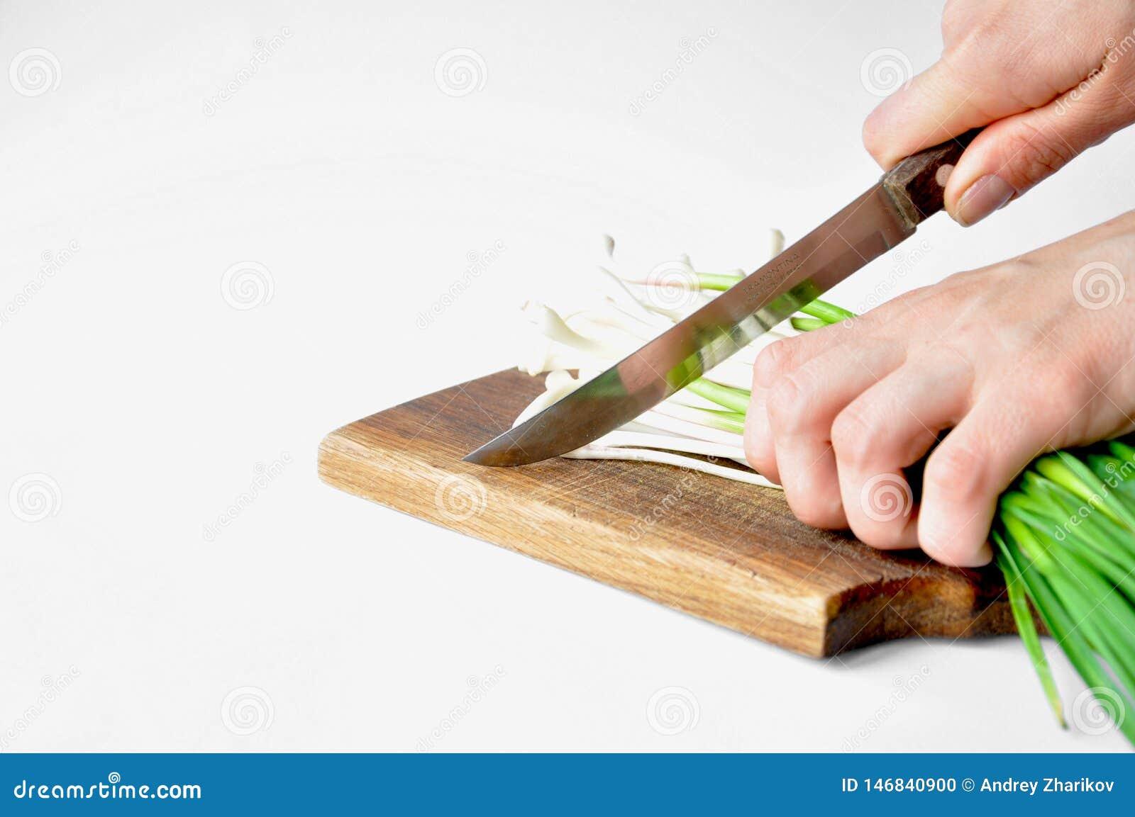Φρέσκο πράσινο σκόρδο στον πίνακα με ένα μαχαίρι