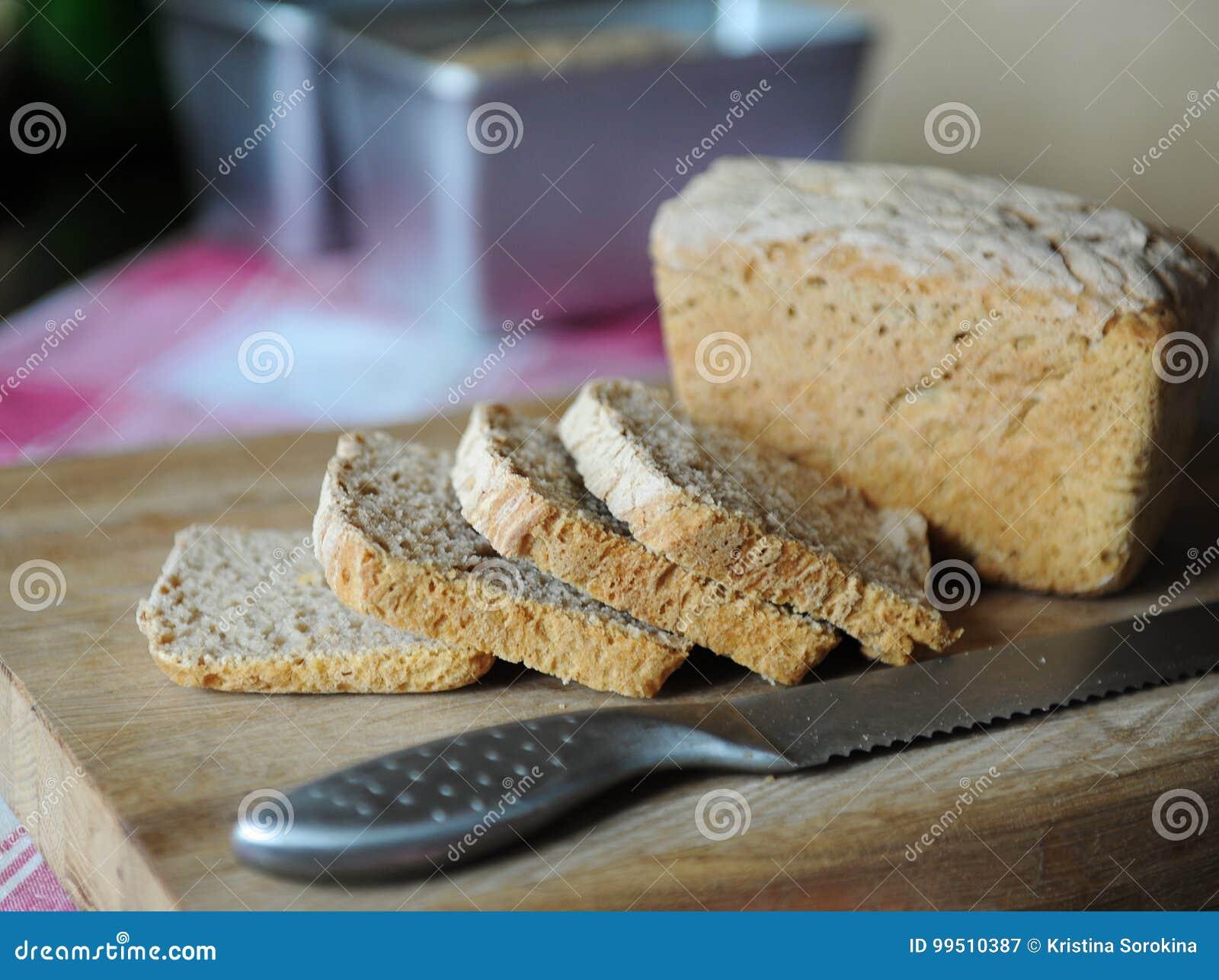 Φρέσκο ψωμί σε ένα ένζυμο σίκαλης χωρίς ζύμη που κόβεται σε έναν ξύλινο τέμνοντα πίνακα σε ένα ελεγμένο τραπεζομάντιλο