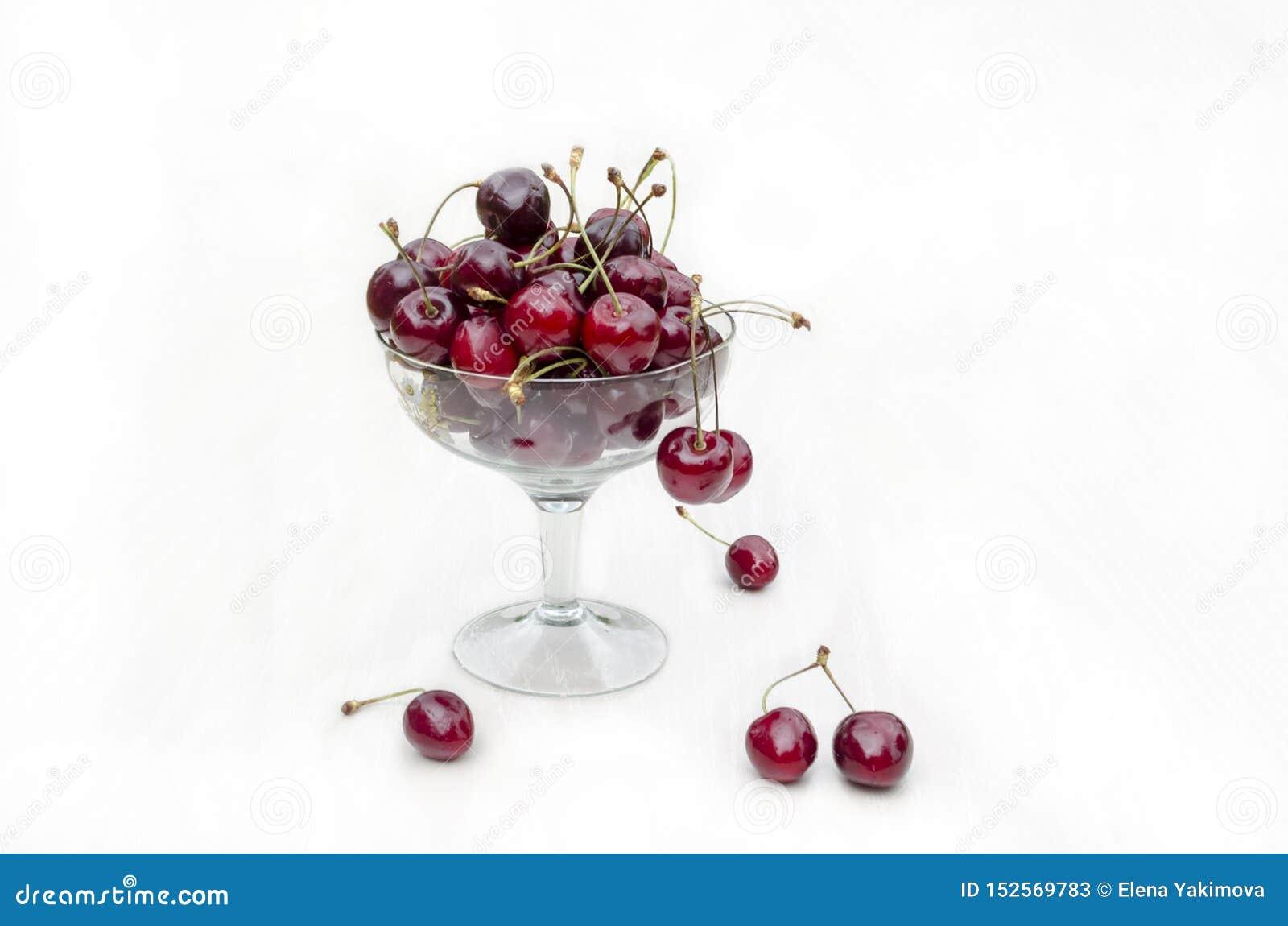 Φρέσκο ώριμο γλυκό κεράσι σε ένα πιάτο γυαλιού κεράσια κεράσι στο κύπελλο στο άσπρο υπόβαθρο