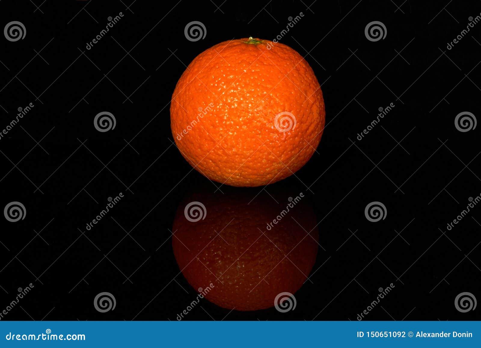 Φρέσκο juicy tangerine με την αντανάκλαση στο Μαύρο