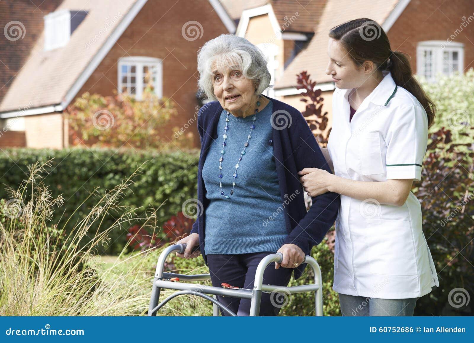 Φροντιστής που βοηθά το ανώτερο άτομο για να περπατήσει στον κήπο που χρησιμοποιεί το πλαίσιο περπατήματος