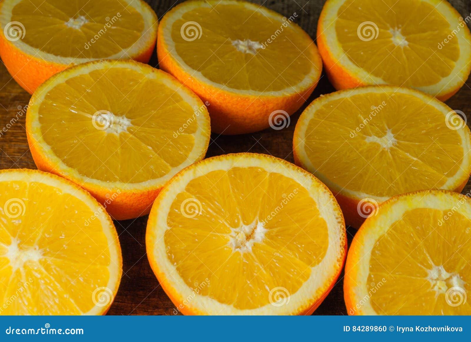 Φρούτα πορτοκαλιών και πορτοκαλιά φέτα στον ξύλινο πίνακα και το αναδρομικό ύφασμα