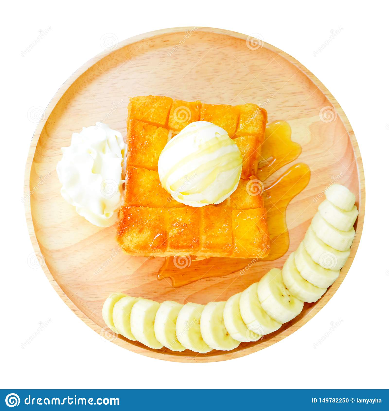 Φρυγανιά μελιού με την μπανάνα στο ξύλινο πιάτο r Πουτίγκα ψωμιού φρυγανιάς με το παγωτό βανίλιας και την κτυπημένη κρέμα που απο