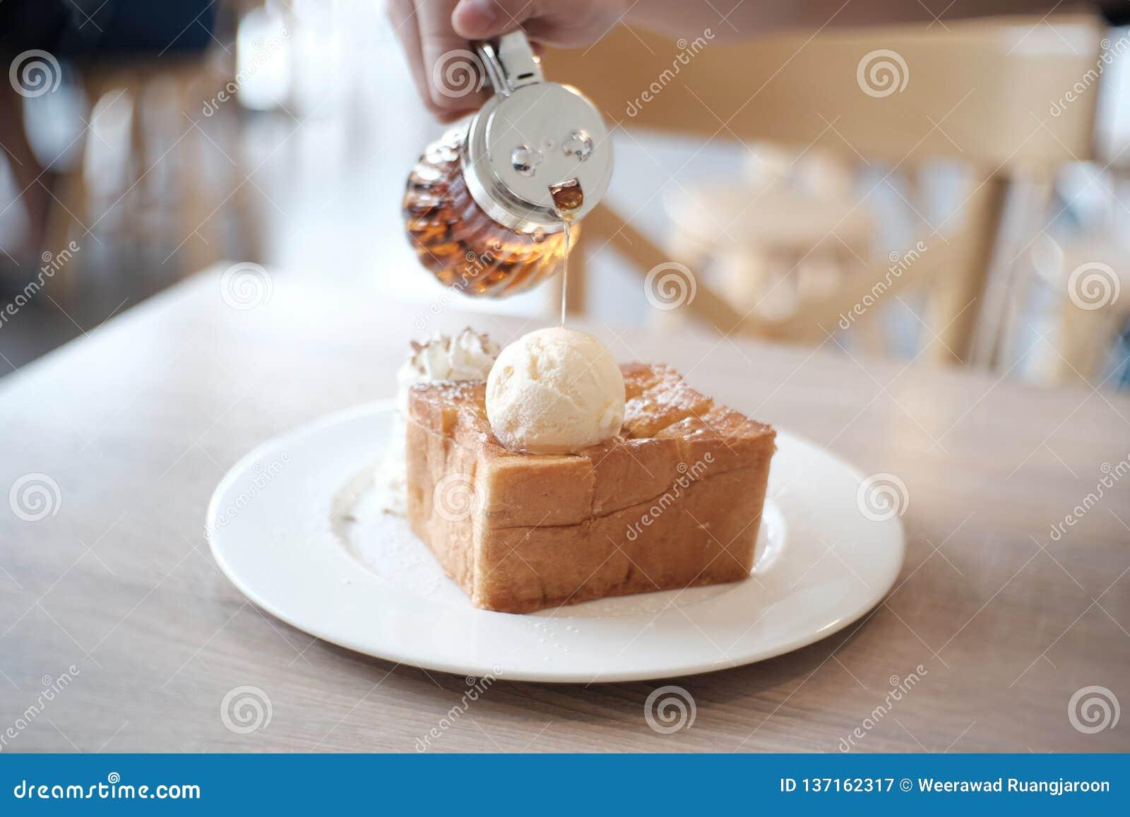 Φρυγανιά μελιού με το παγωτό βανίλιας και κτυπημένη κρέμα στο άσπρο πιάτο