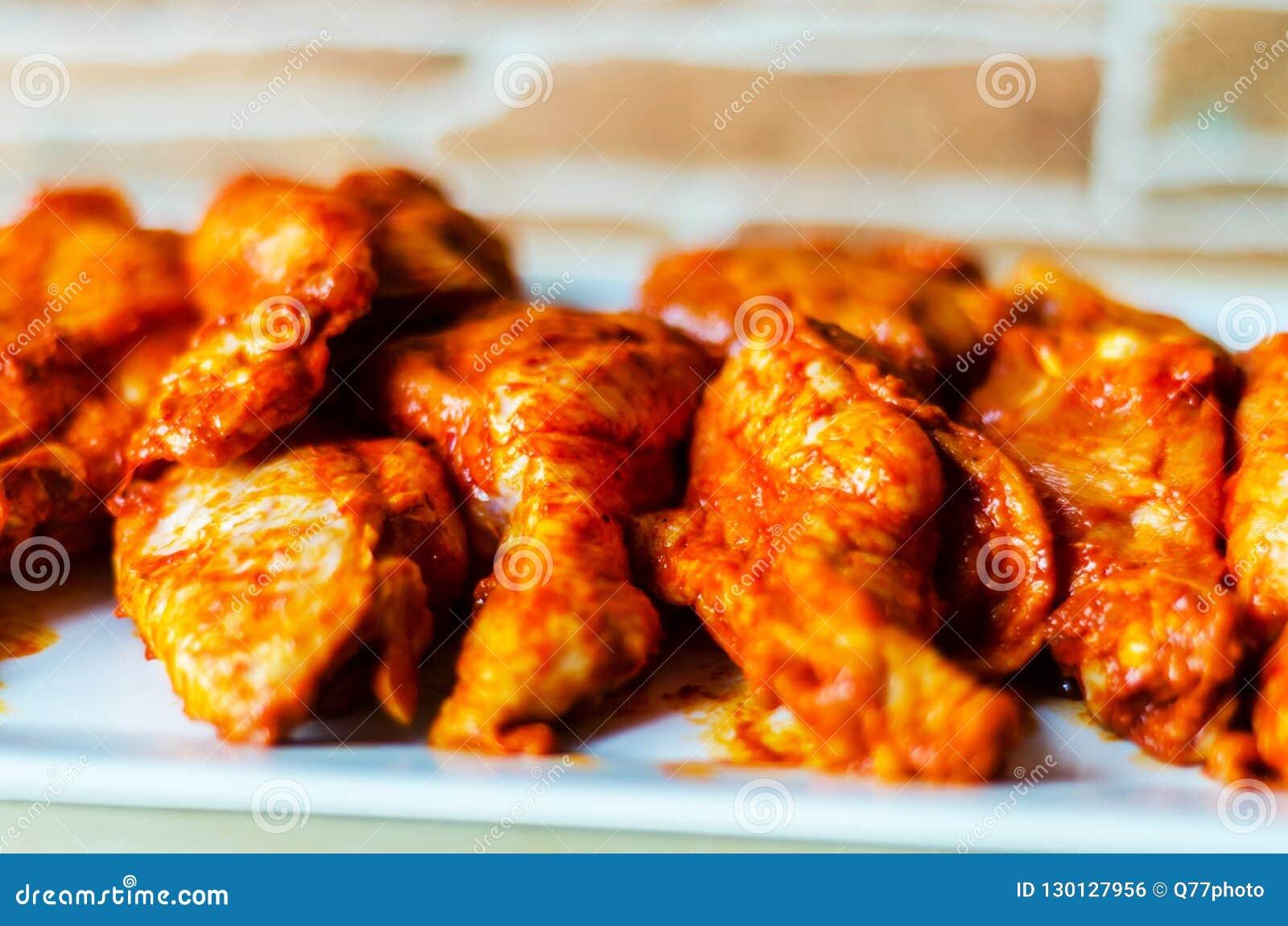 Φτερά κοτόπουλου που μαρινάρονται σε μια σάλτσα σχαρών, ένας χαρακτηριστικός Αμερικανός