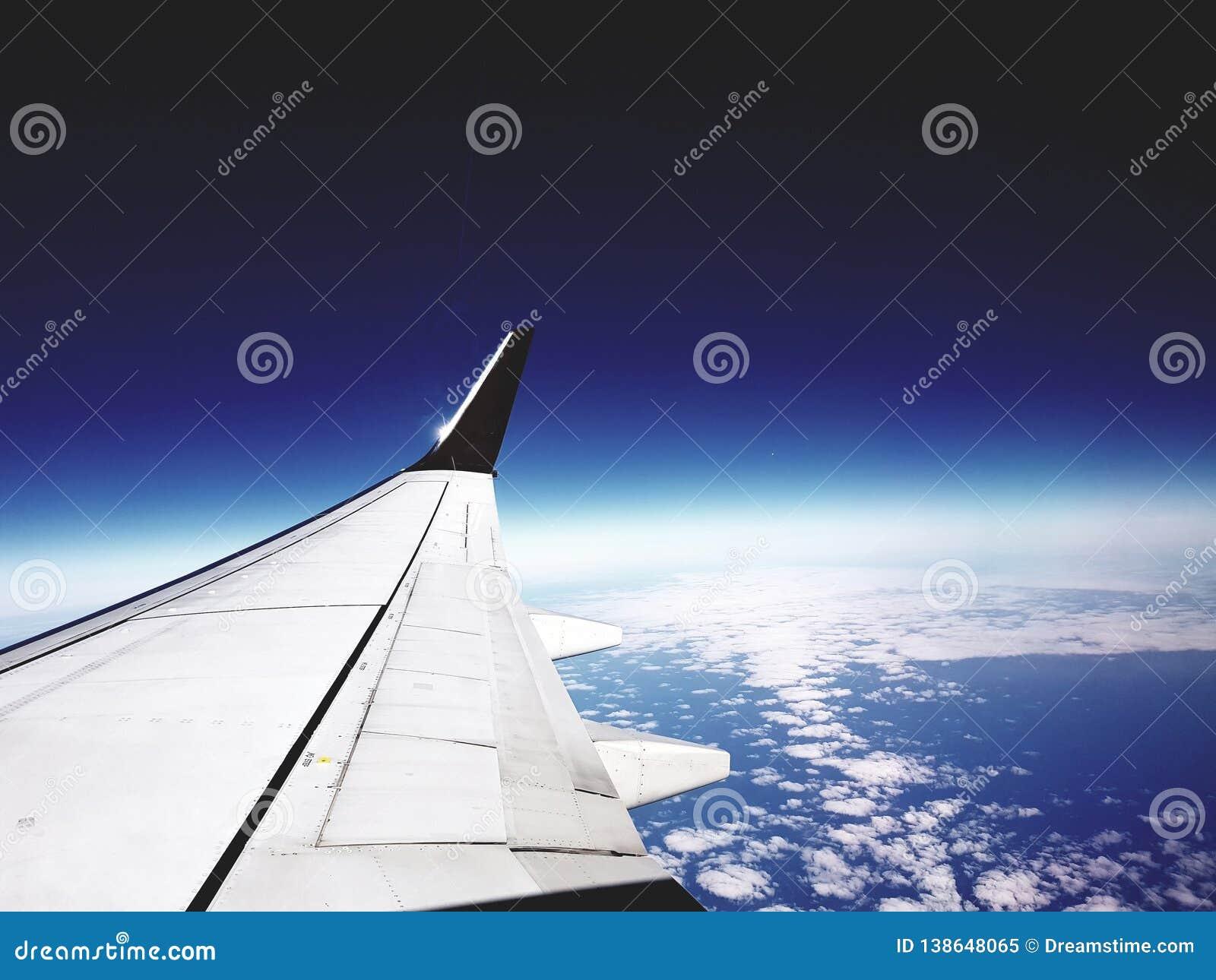 Φτερό αεροπλάνων πέρα από τη νεφελώδη γήινη επιφάνεια με το σκούρο μπλε ορίζοντα