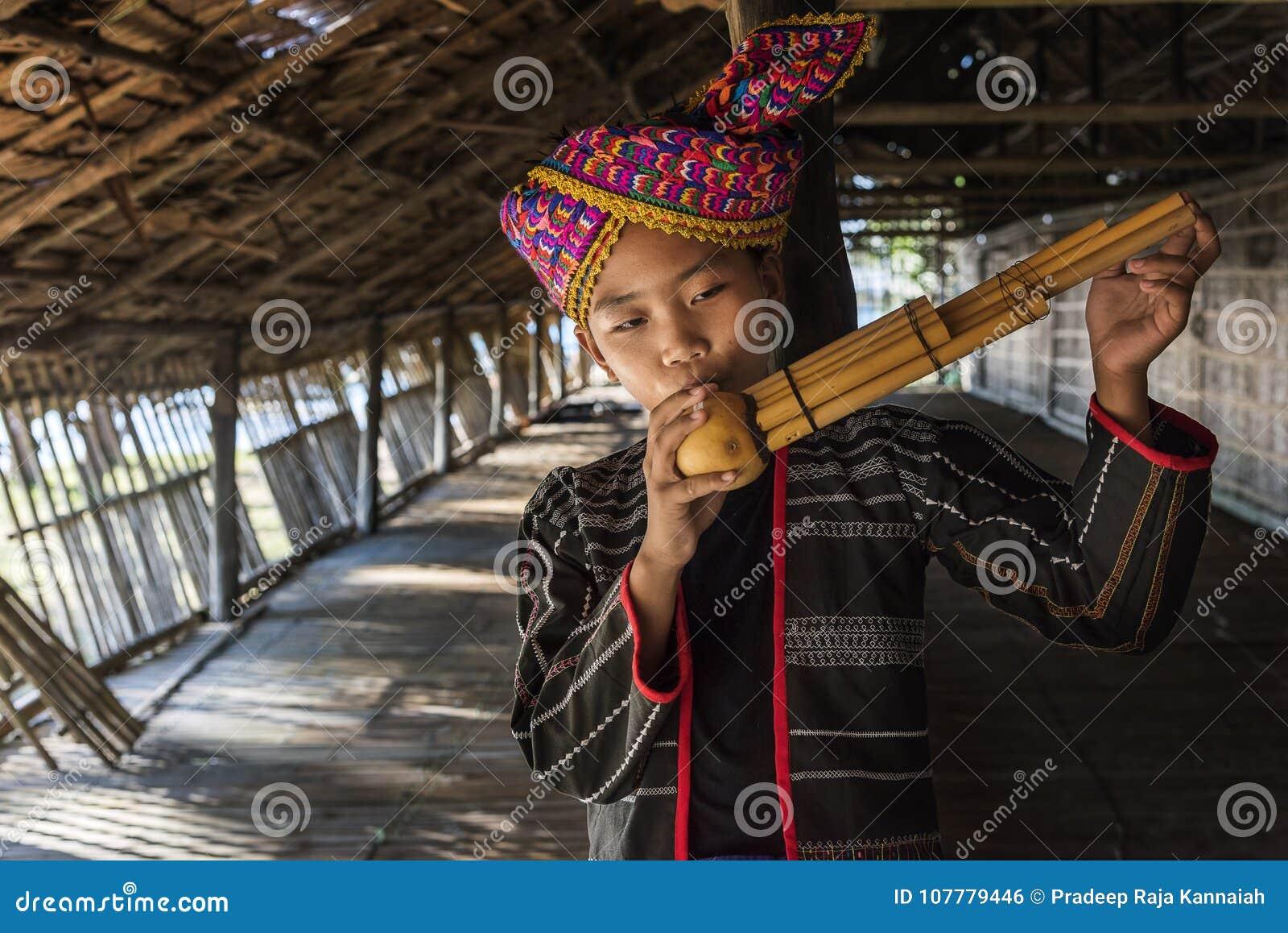 Φυλετικό αγόρι Rangus στο παραδοσιακό κοστούμι του που παίζει Sompoton που αποτελείται από τους σωλήνες μπαμπού, Kudat Μαλαισία