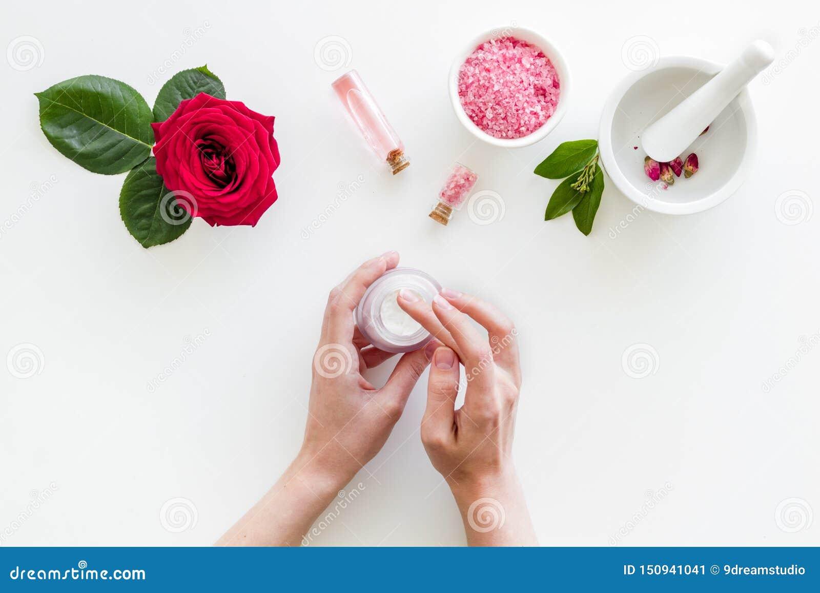 Φυσικά οργανικά καλλυντικά με το ροδαλό απόσπασμα στα χέρια στην άσπρη τοπ άποψη υποβάθρου