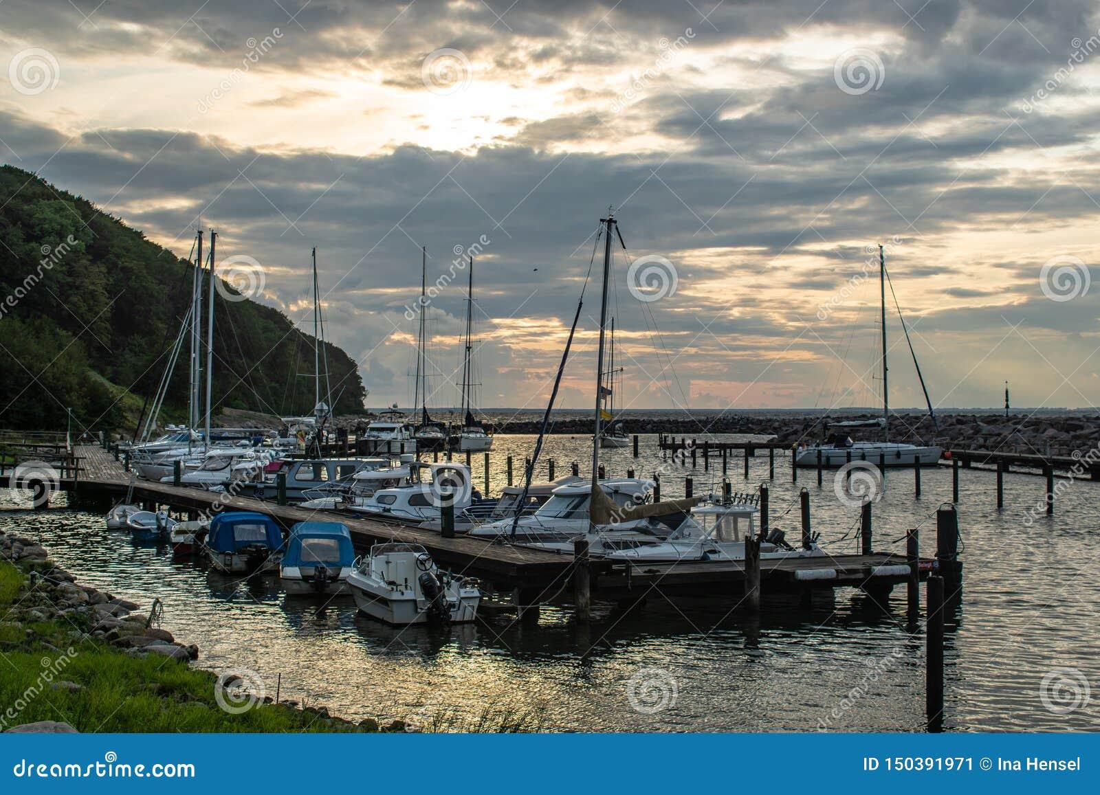 Φυσικός λίγο λιμάνι με τις πλέοντας βάρκες στο φως ηλιοβασιλέματος