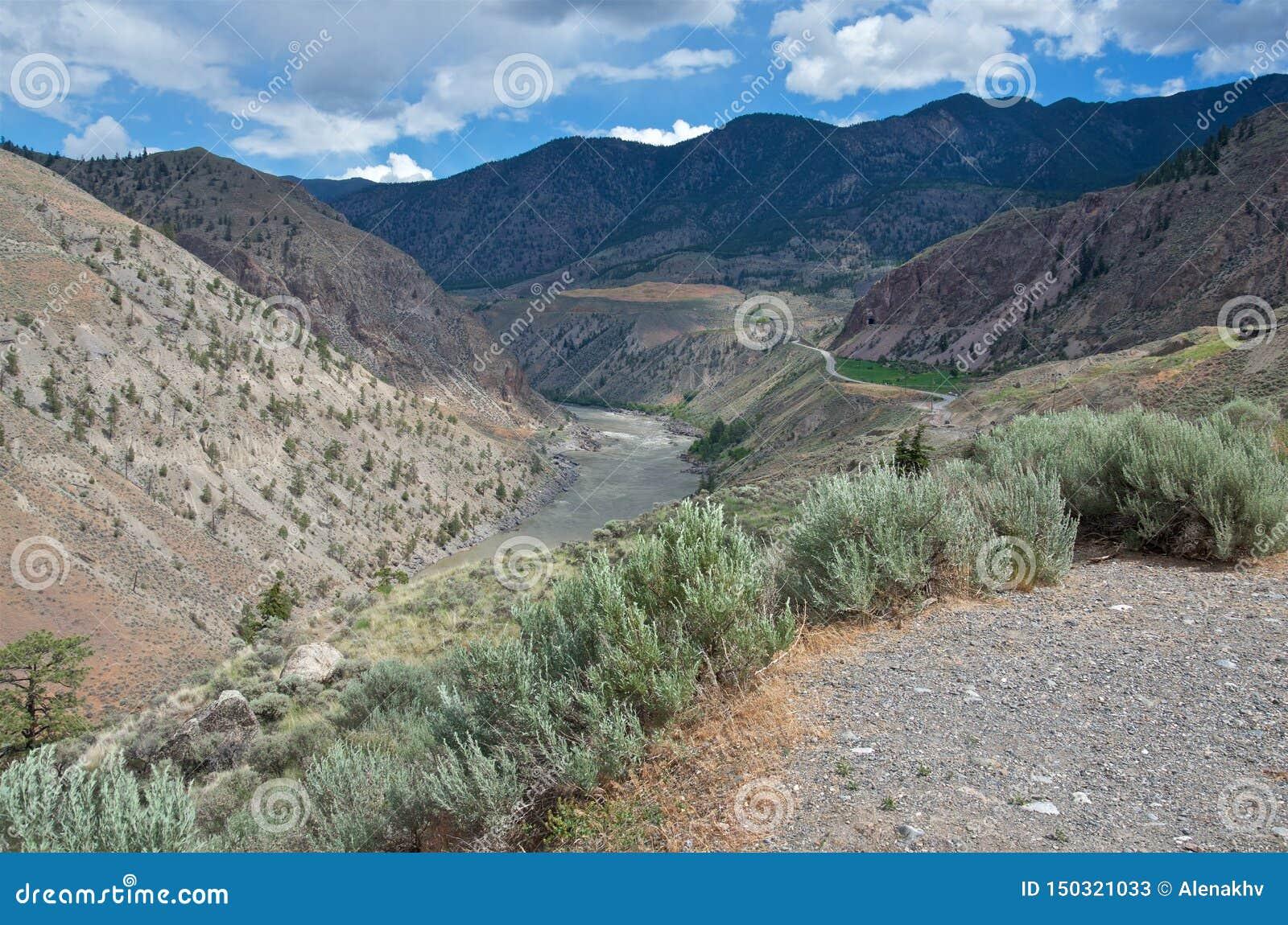 Φυσικό φαράγγι ερήμων του λασπώδους ποταμού Fraser στο νεφελώδη καιρό το καλοκαίρι