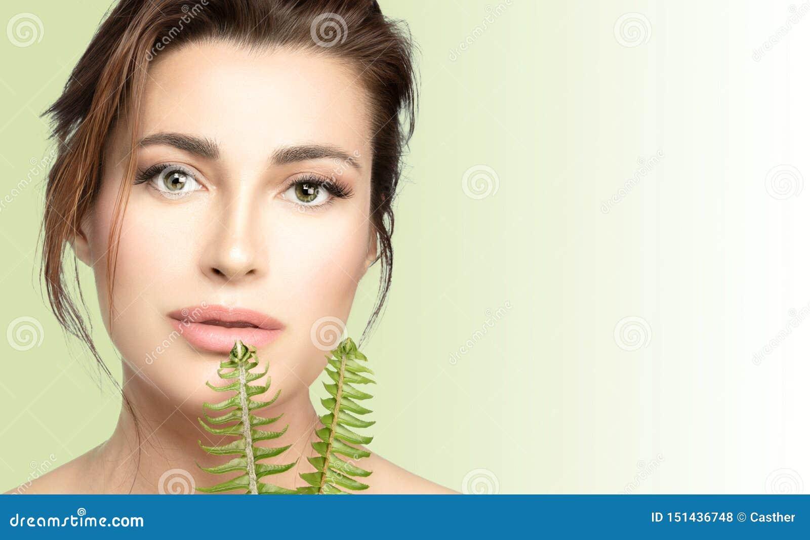 Φυσικό skincare Beauty Spa γυναίκα με τα φρέσκα πράσινα φύλλα Υγεία και έννοια θεραπείας SPA