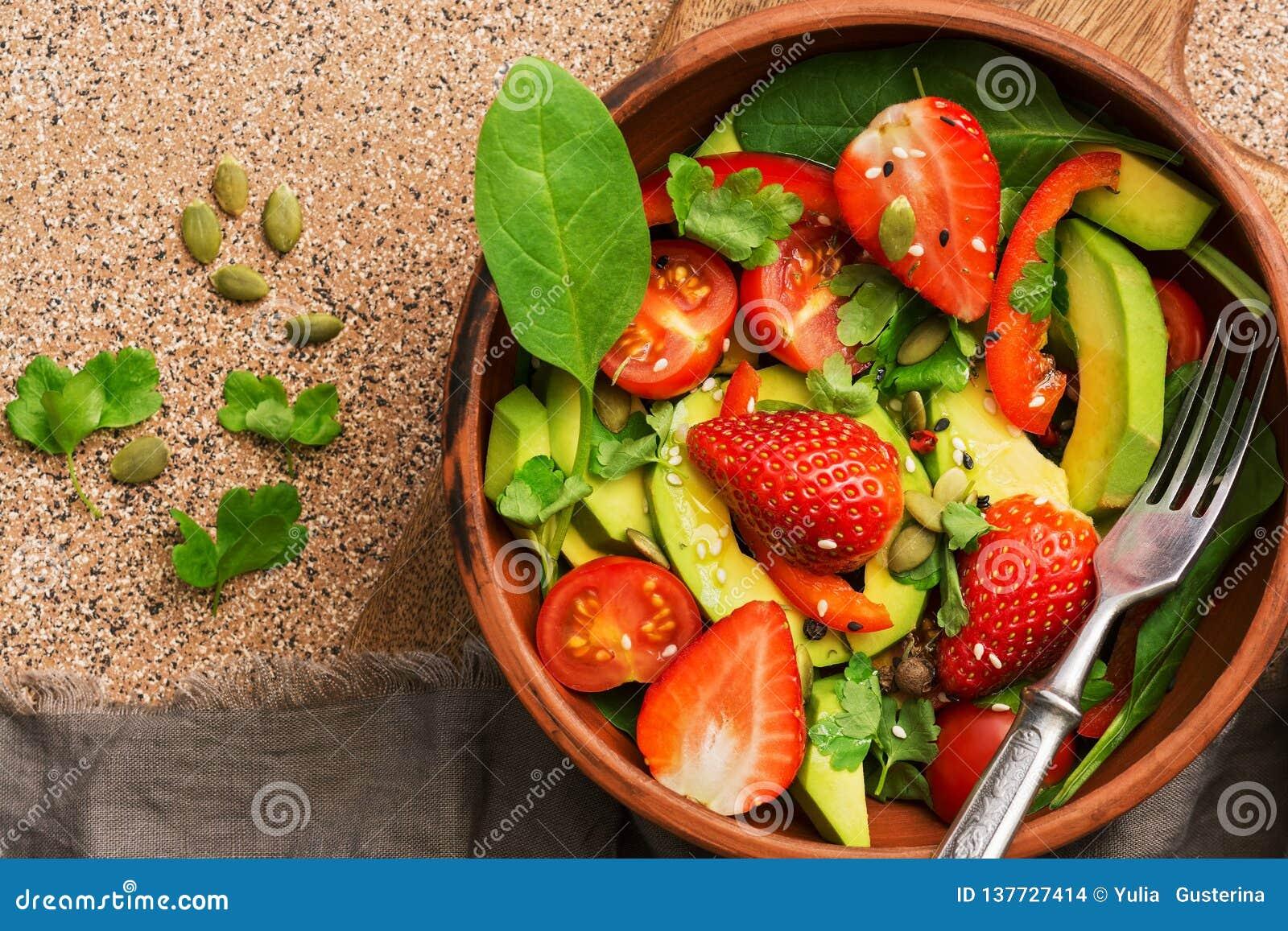 Φυτική υγιής χορτοφάγος σαλάτα, αβοκάντο, σπανάκι, φράουλα, ντομάτα, πράσινα, γλυκά πιπέρια, σπόροι Τοπ άποψη, διάστημα αντιγράφω