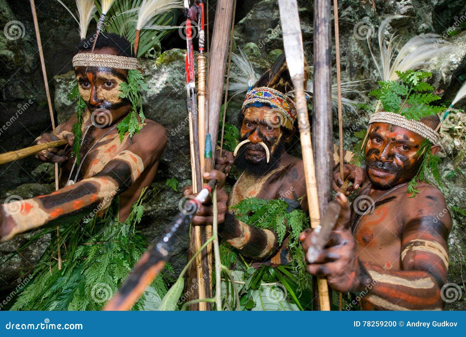 Φυλή Yaffi πολεμιστών στο πολεμικό χρώμα με τα τόξα και τα βέλη στη σπηλιά Νησί της Νέας Γουϊνέας